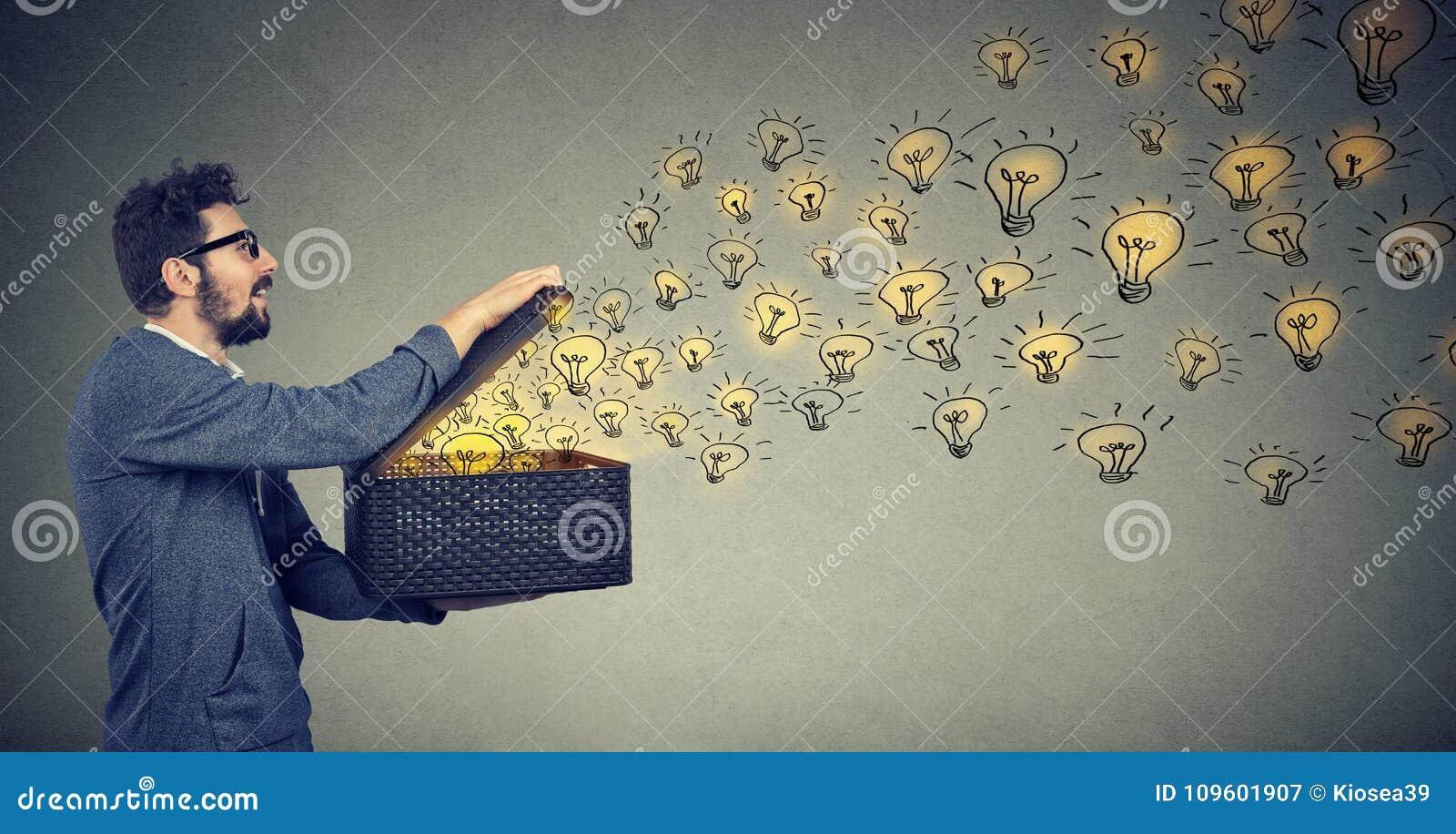 Sidosikt av en lycklig maninnehavask med briljanta idéer som är idérik och fördelande kunskap