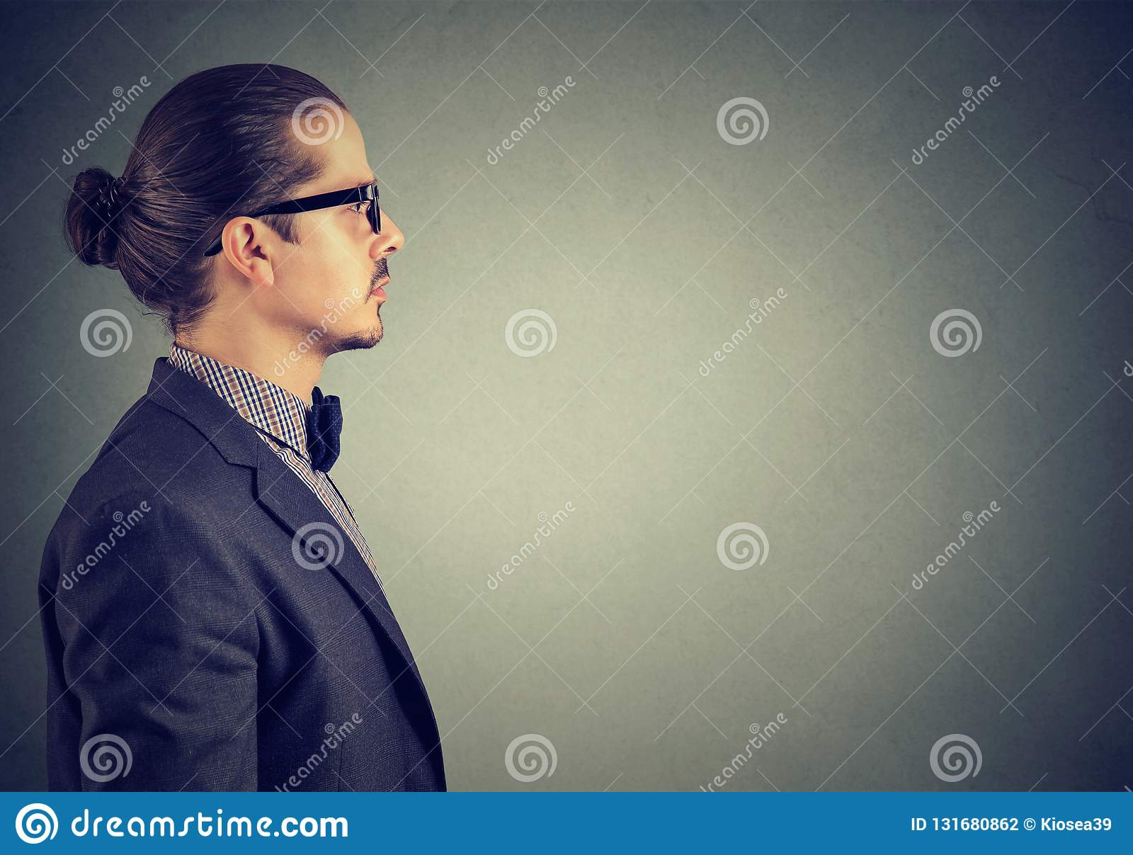 Sidosikt av en vuxen man i dräkten som ser allvarlig på grå bakgrund