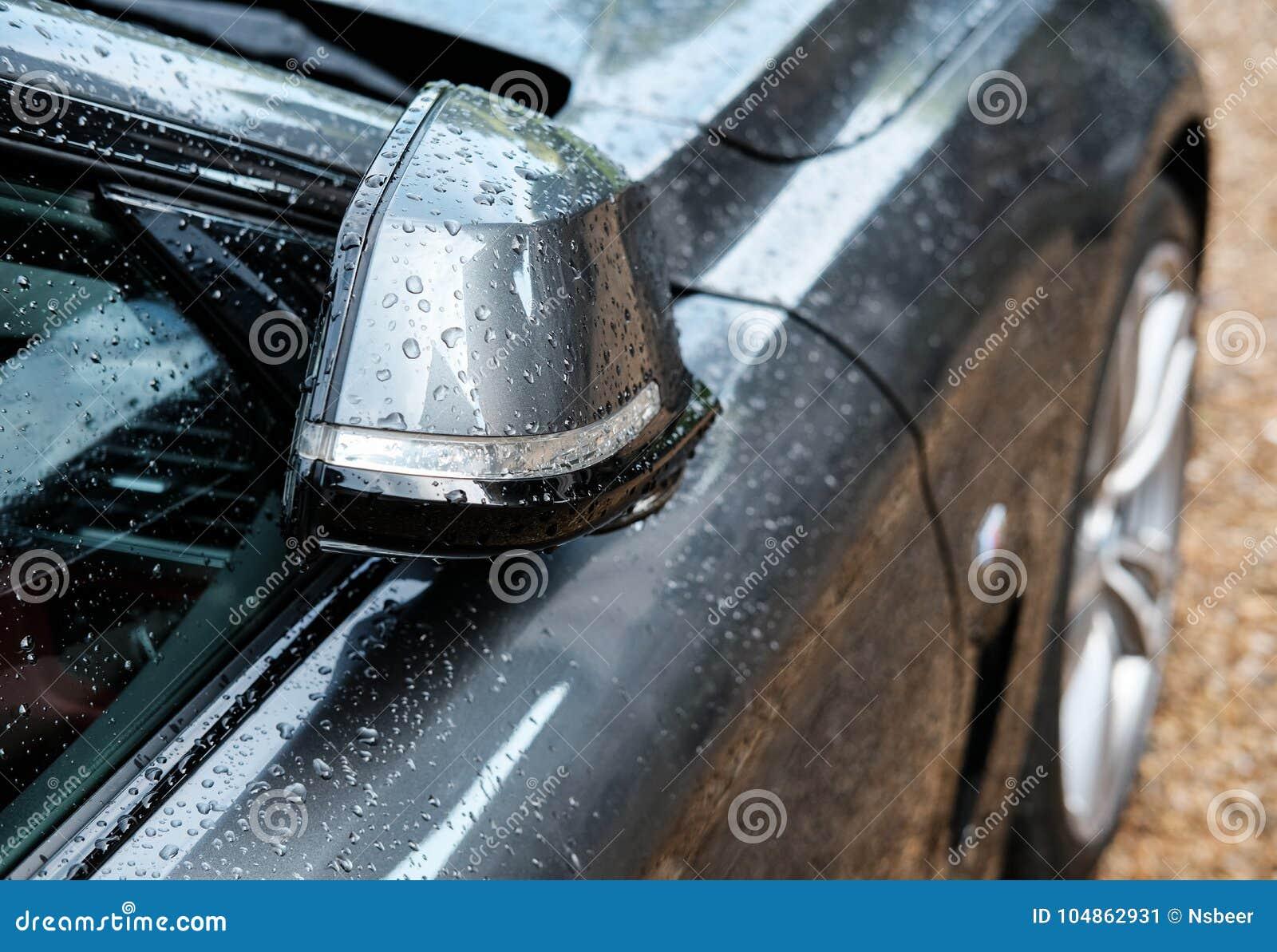 Sidosikt av engjord lyxig sportbil som ses efter en tung hällregn i en återförsäljare