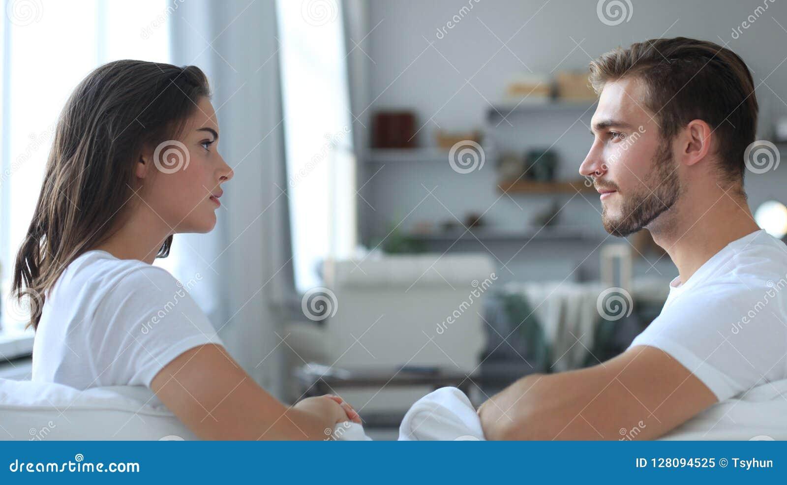 Sidosikt av ett talande sammanträde för par på en soffa och att se sig hemma