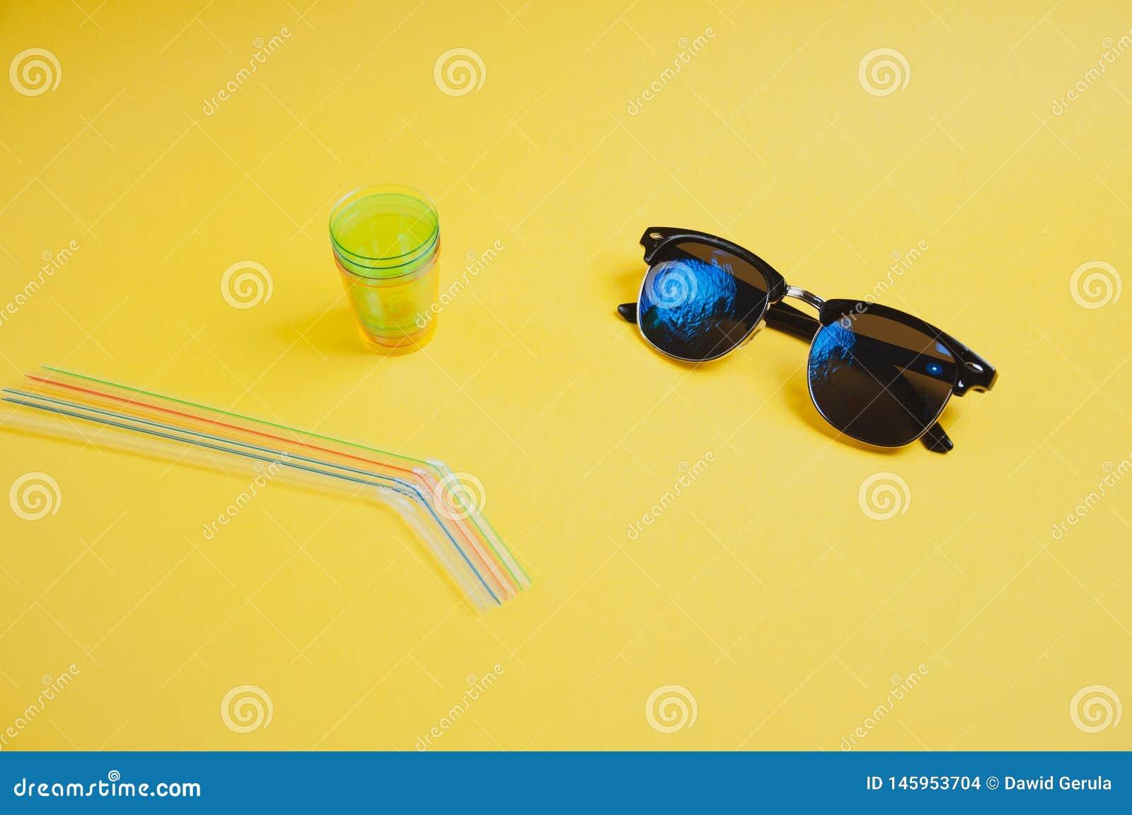 Sidosikt av f?rgrika sugr?r, exponeringsglas och solglas?gon p? gul bakgrund, med kopieringsutrymme