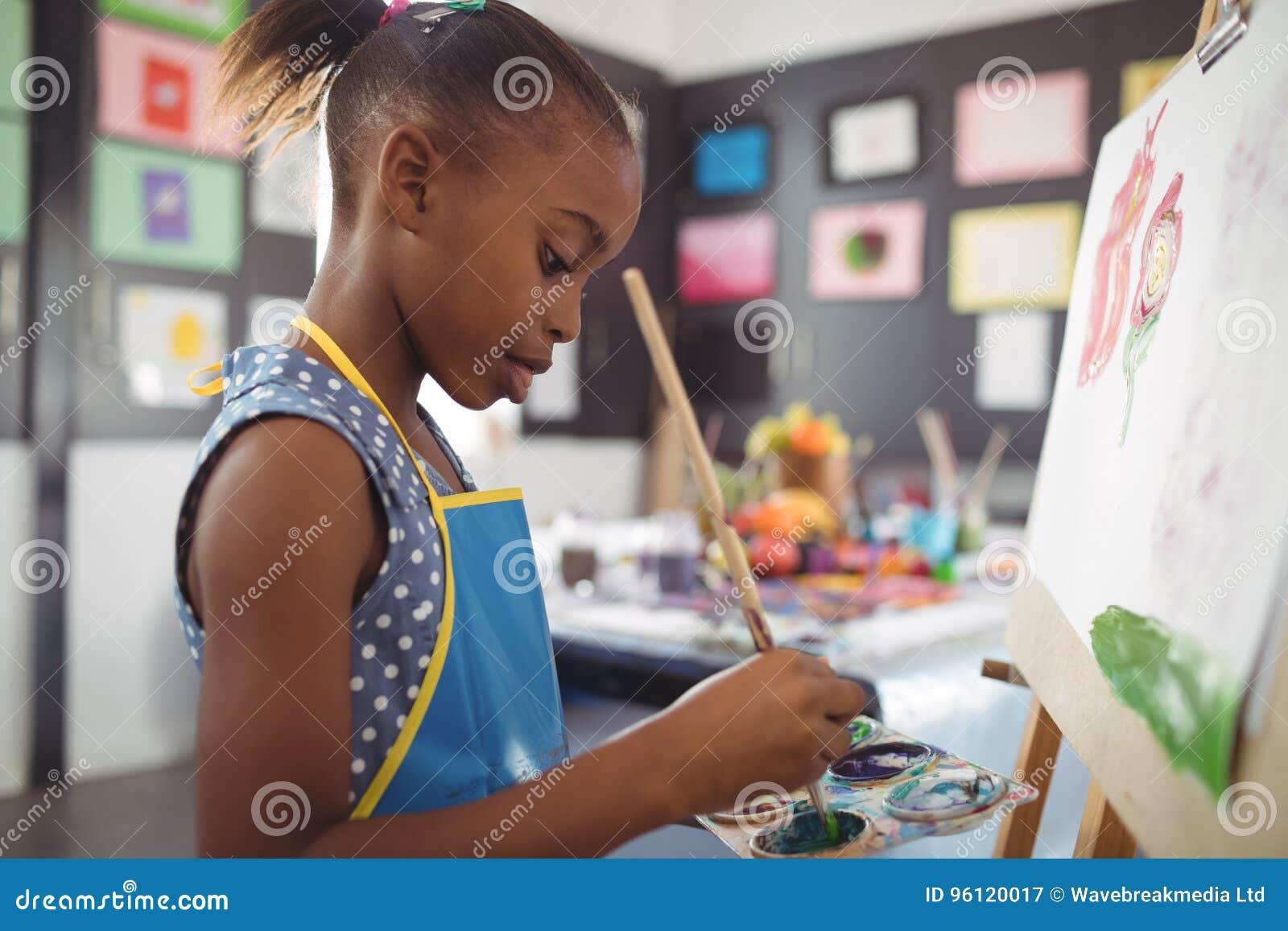 Sidosikt av fokuserad flickamålning på kanfas