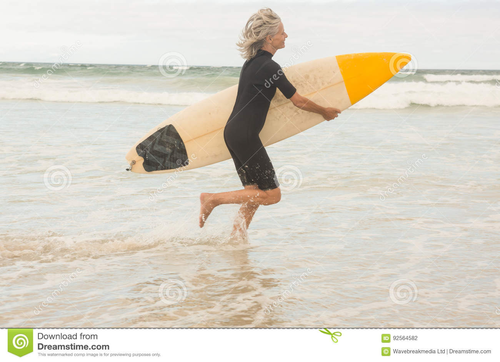 Sidosikt av kvinnaspring med surfingbrädan på kust