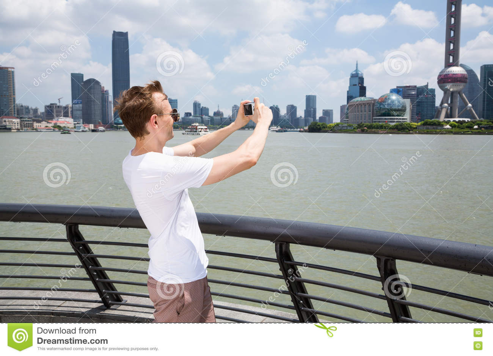 Sidosikt av mannen som fotograferar byggnader, medan stå vid räcket i Shanghai