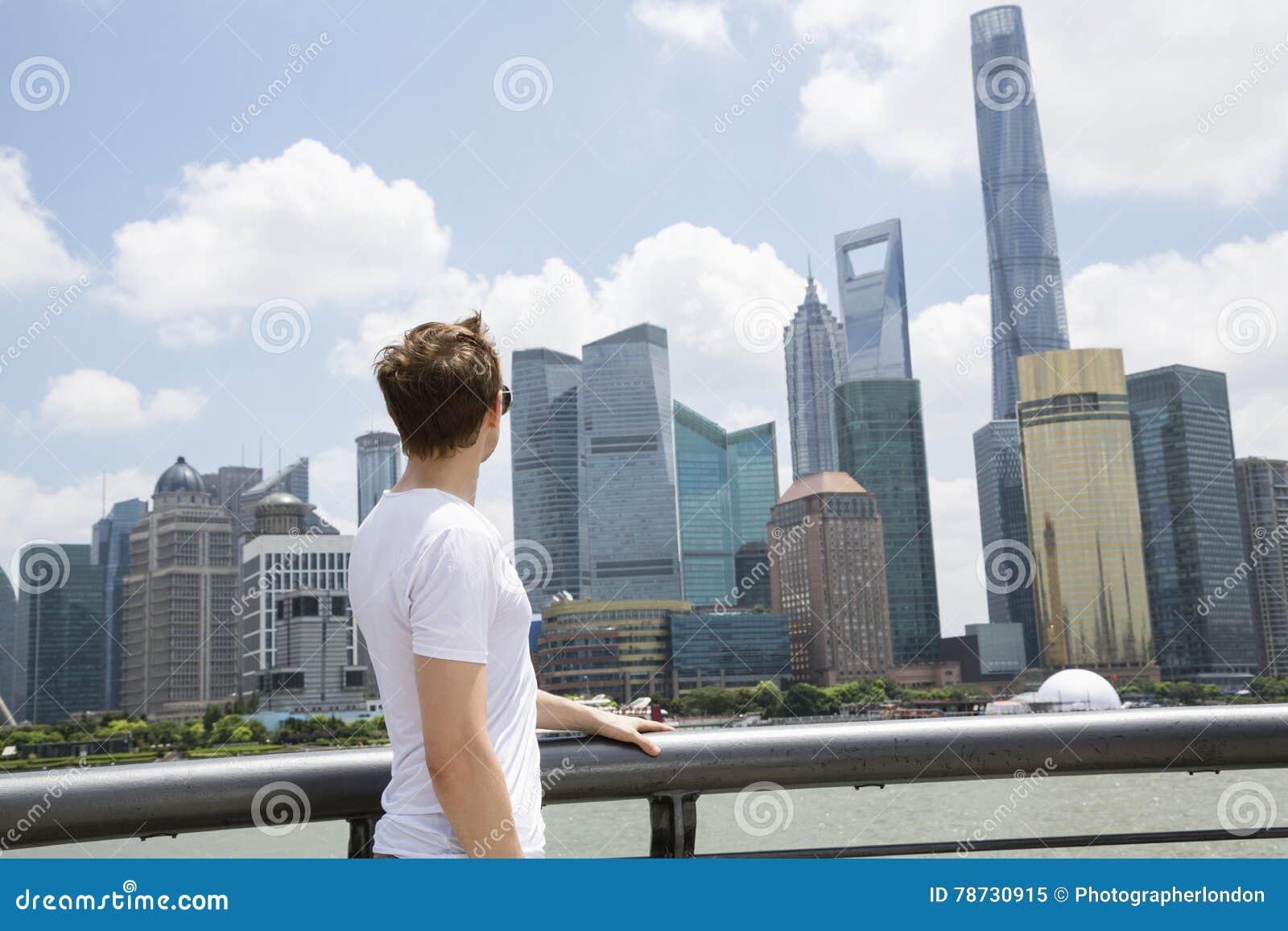 Sidosikt av mannen som ser den finansiella mitten för Shanghai värld mot molnig himmel