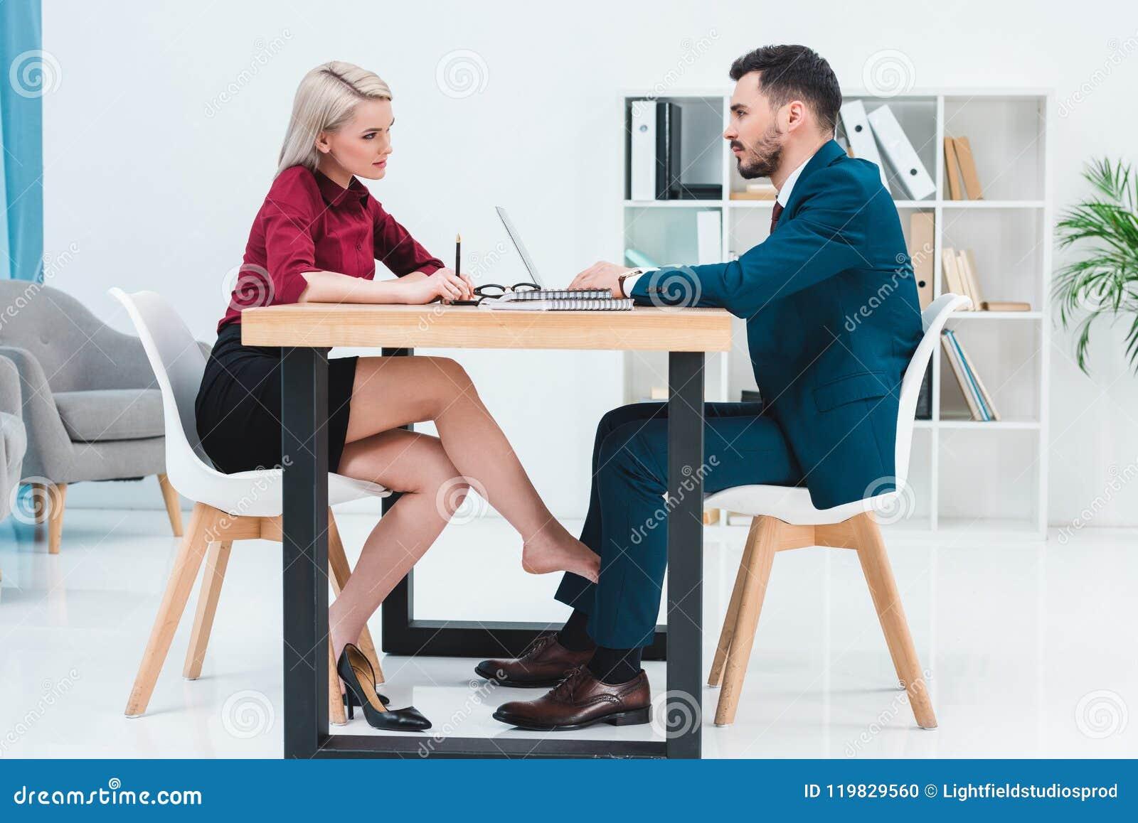 Sidosikt av unga par av affärsfolk som ser de, medan arbeta tillsammans och flörta under tabellen