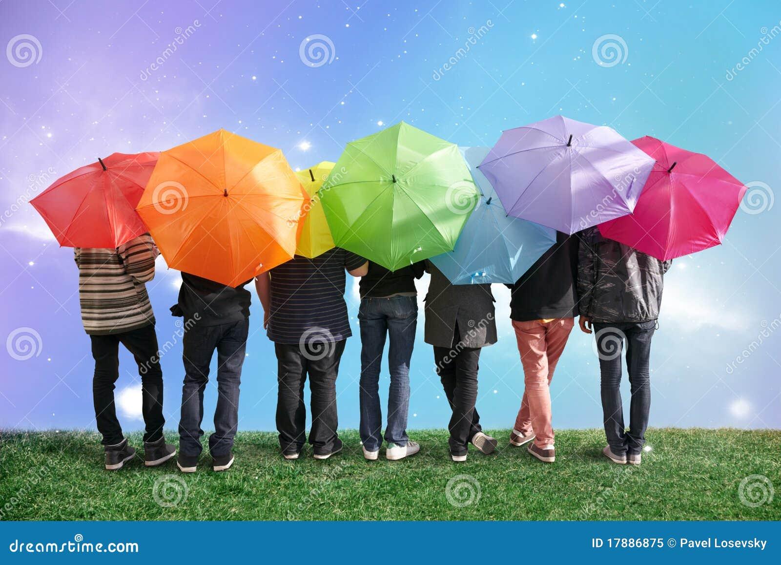 Sieben Freunde mit Regenbogenfarbenregenschirmen