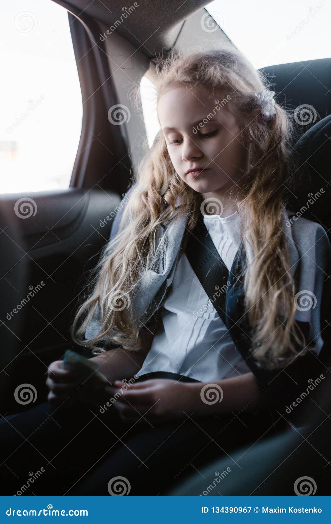 Siebenjähriges reizend Mädchen, das in einem Autositz der Kinder sitzt