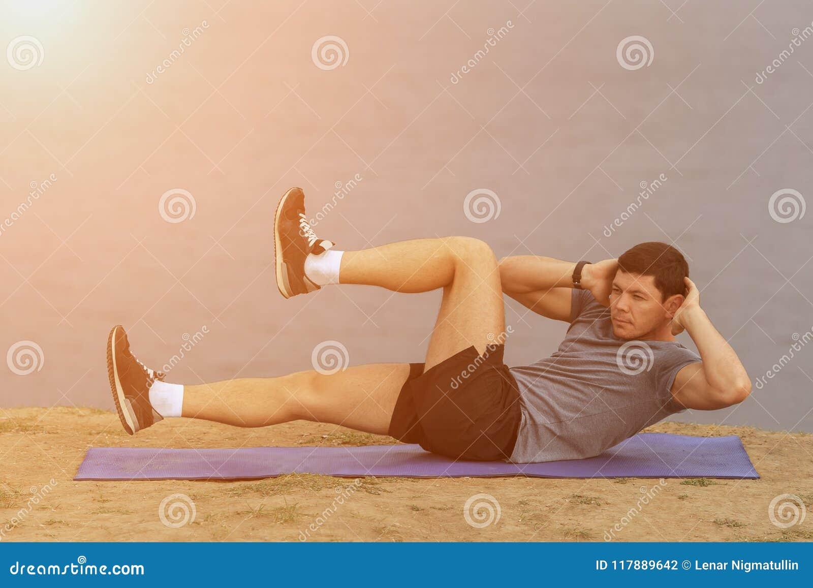 Siedzi podnosi - sprawność fizyczna mężczyzna ćwiczyć siedzi up outside w trawie w lecie Dysponowanej męskiej atlety pracujący pr