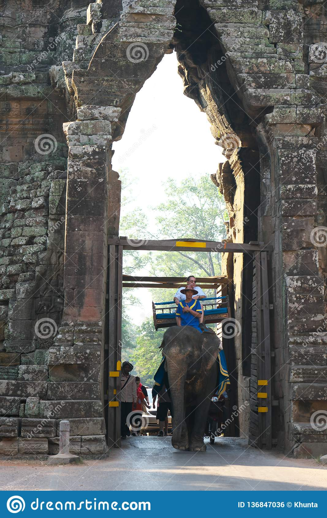 Tourists pass the south gate of Angkor Thom on an elephant