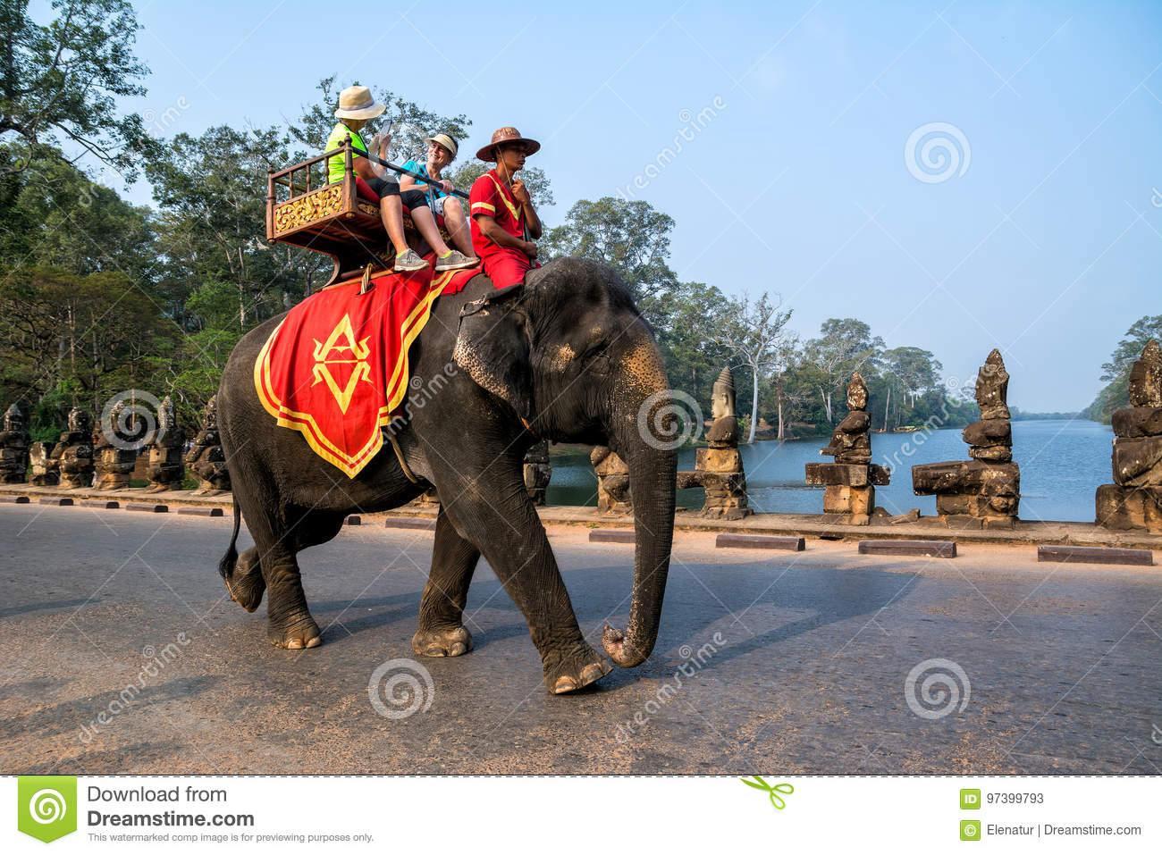 SIEM REAP, CAMBODIA - MARCH 8, 2017: An elephant carrying tourists over causeway near Gate of Angkor Thom on March 8, 2017 in