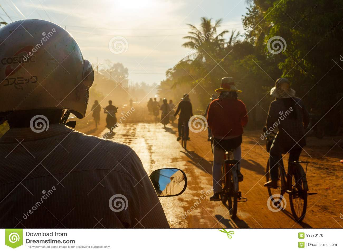Bicycles and motorbikes on a dirt road in Cambodia