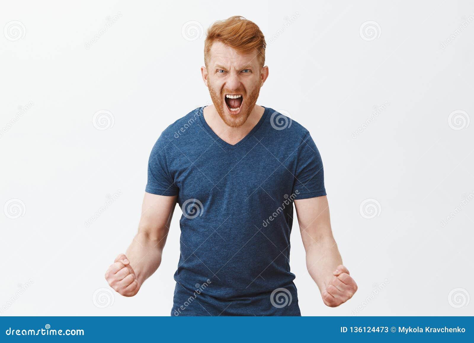 Sienta mi furia Retrato del varón masculino fuerte enojado y cabreado ultrajado del pelirrojo con la cerda, puños de apretón en c