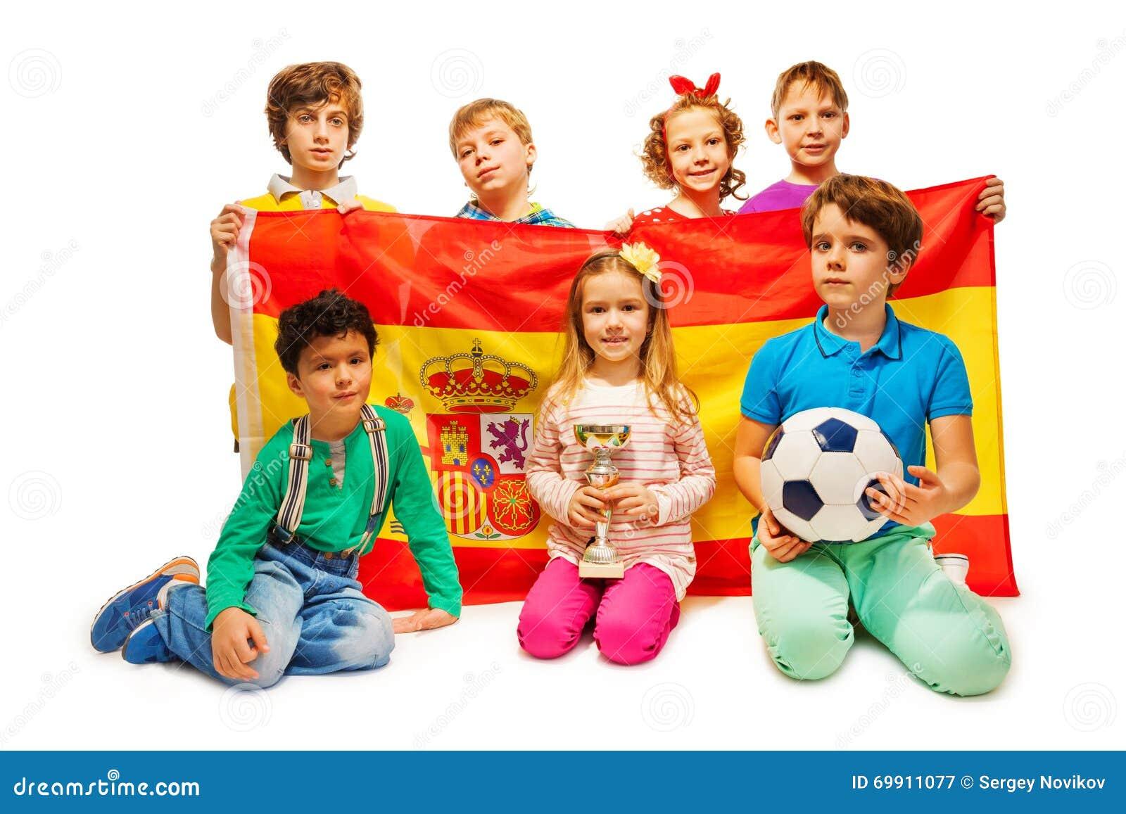 Siete fanáticos del fútbol con la bola que sostiene la bandera española