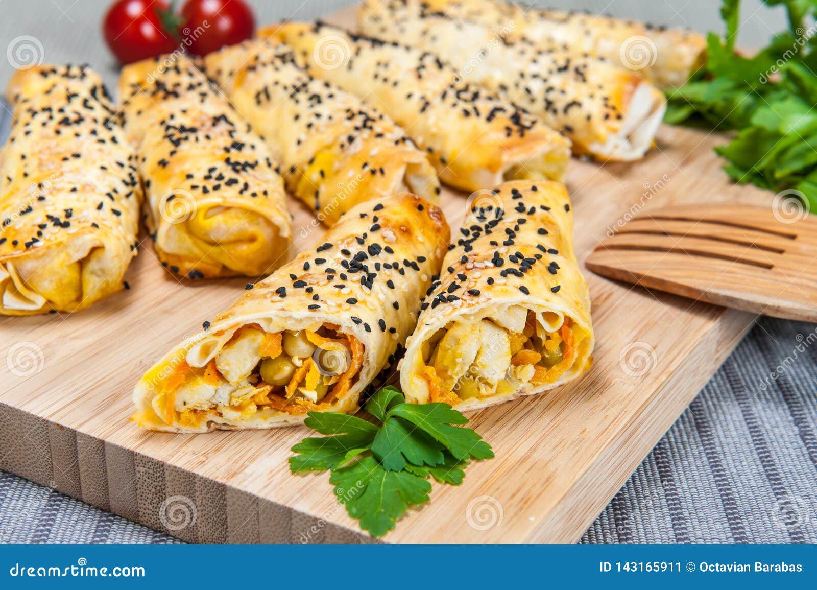 Sigaar gevormd bakkerijbroodje met kip en groenten op houten raad