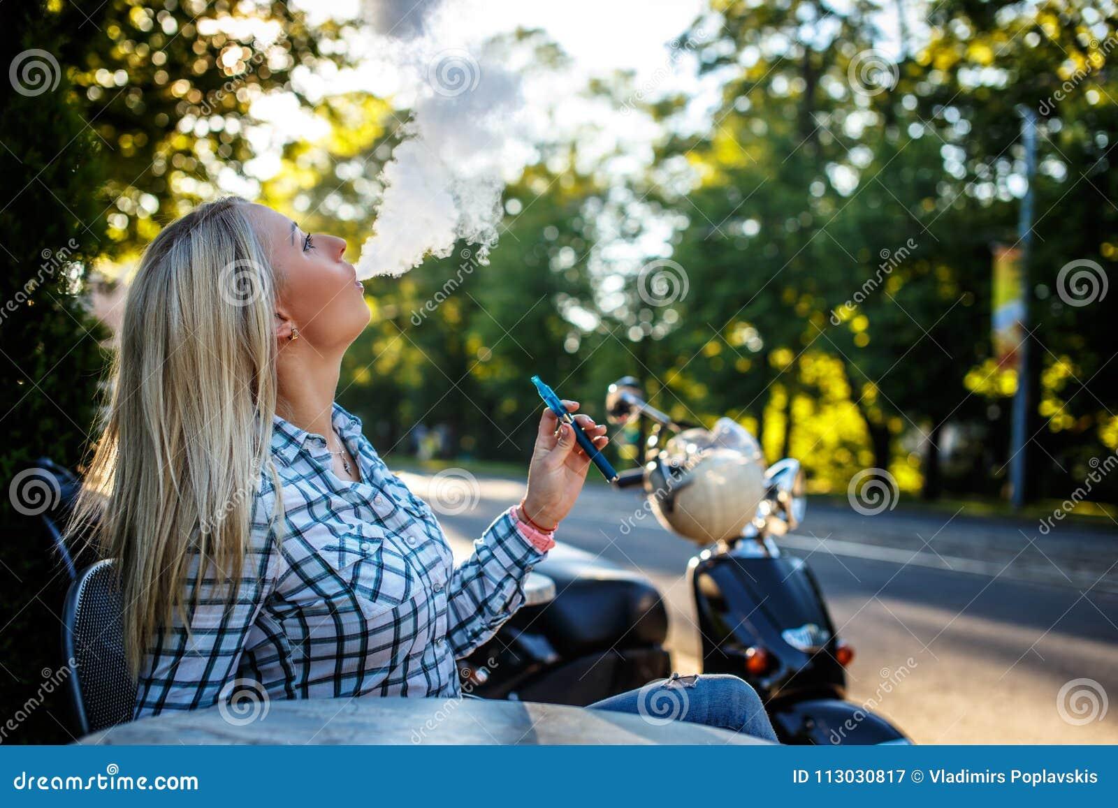 Sigarette que fuma de la mujer