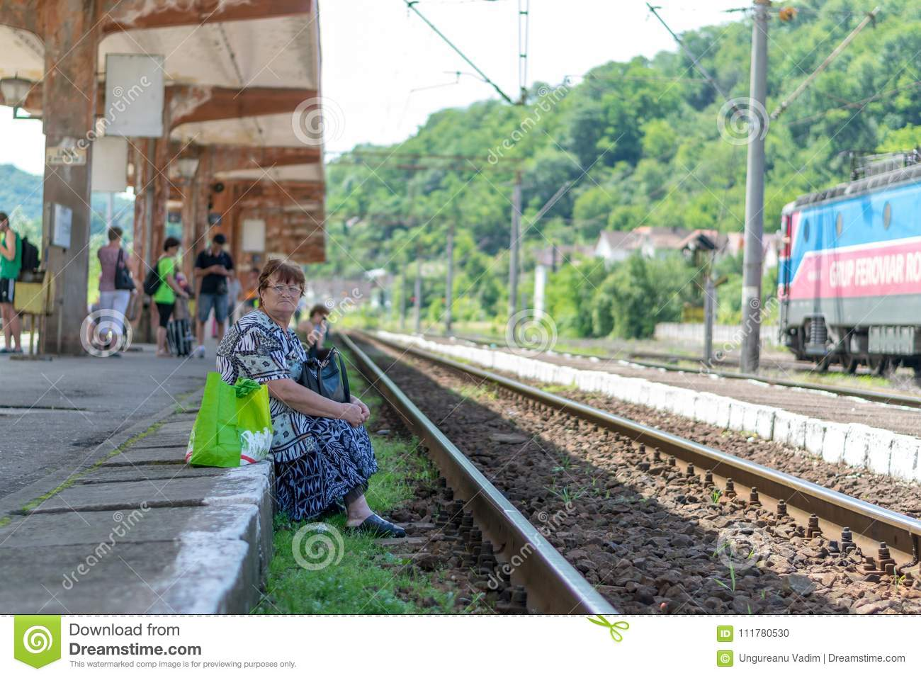 SIGHISOARA, ROMANIA - 1 JULY 2016: Older woman waiting for the train in Sighisoara, Romania.