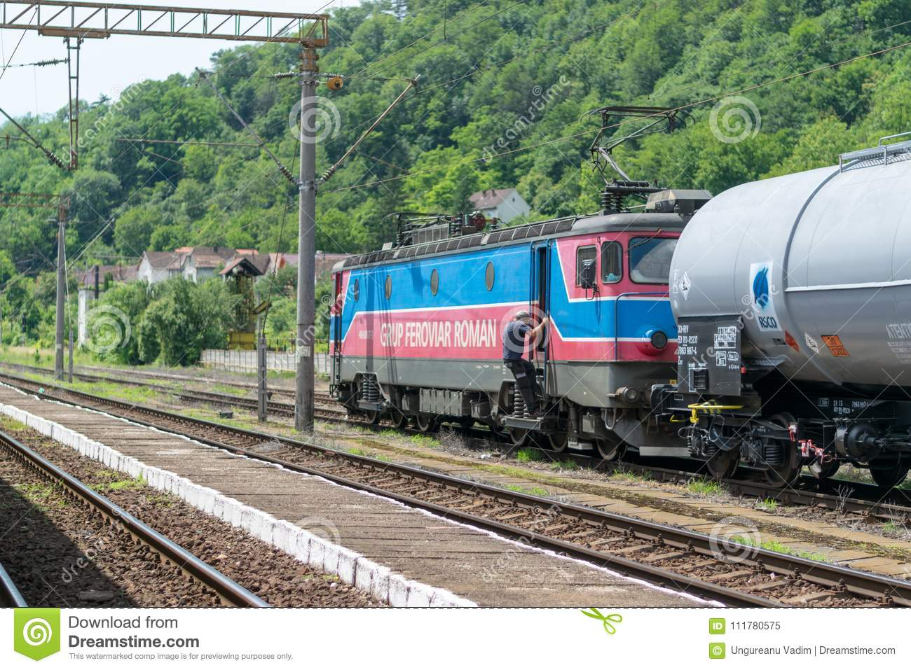 SIGHISOARA, ROMANIA - 1 JULY 2016: Train conductor get on the train locomotive with cargo wagons at the Sighisoara train station i