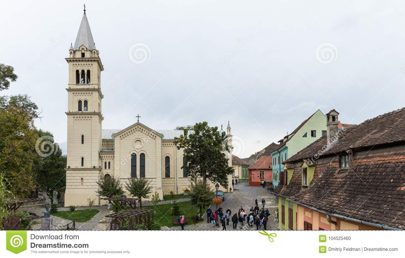 Tourists walk around the square near Roman Catholic Church - Citadel in the castle of old city. Sighisoara city in Romania