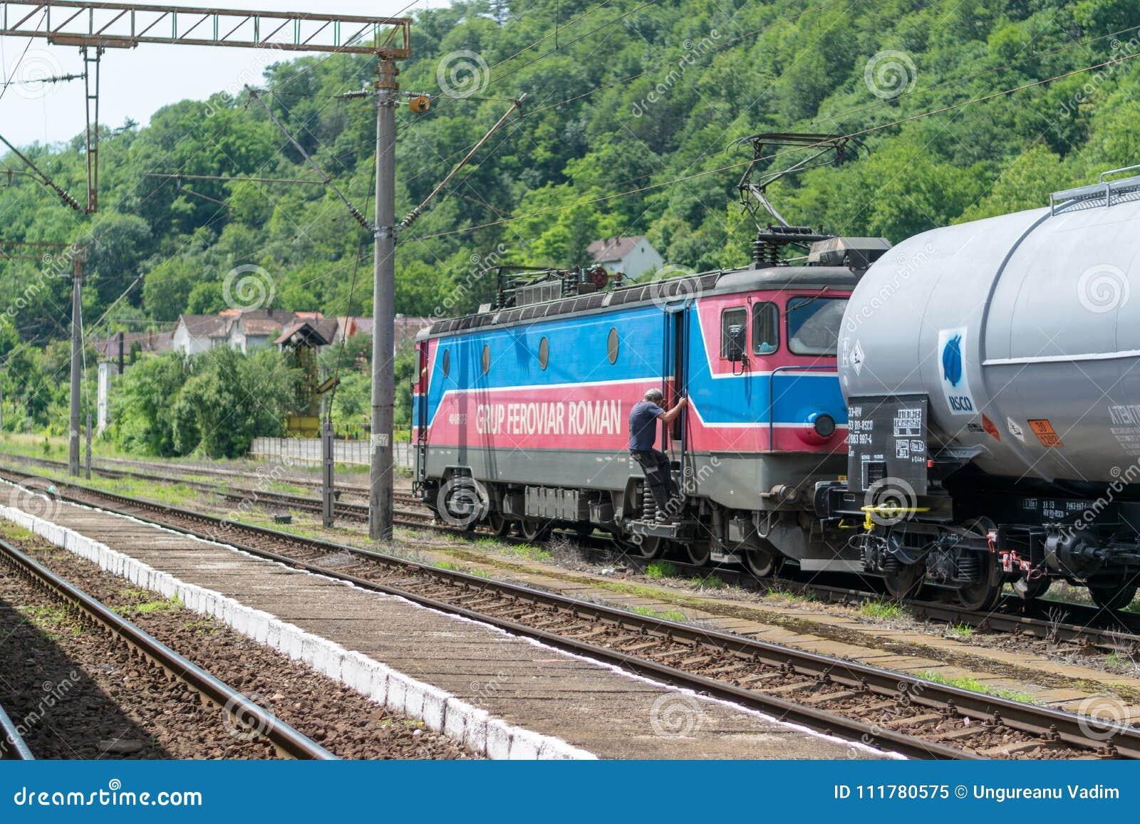 SIGHISOARA RUMÄNIEN - 1 JULI 2016: Drevledaren får på drevlokomotivet med lastvagnar på den Sighisoara drevstationen I