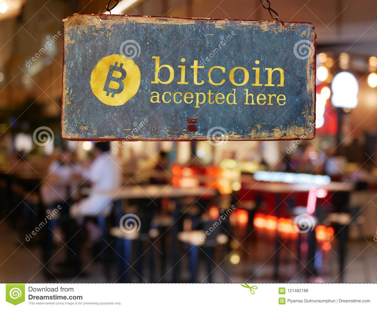 Sign bitcoin accepted here hanging in front of restaurant door.