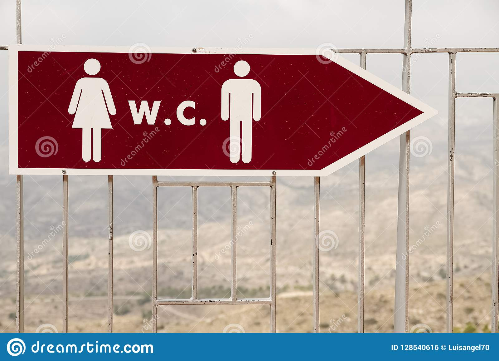 Sign indicating the location of the bathrooms in a mountain area