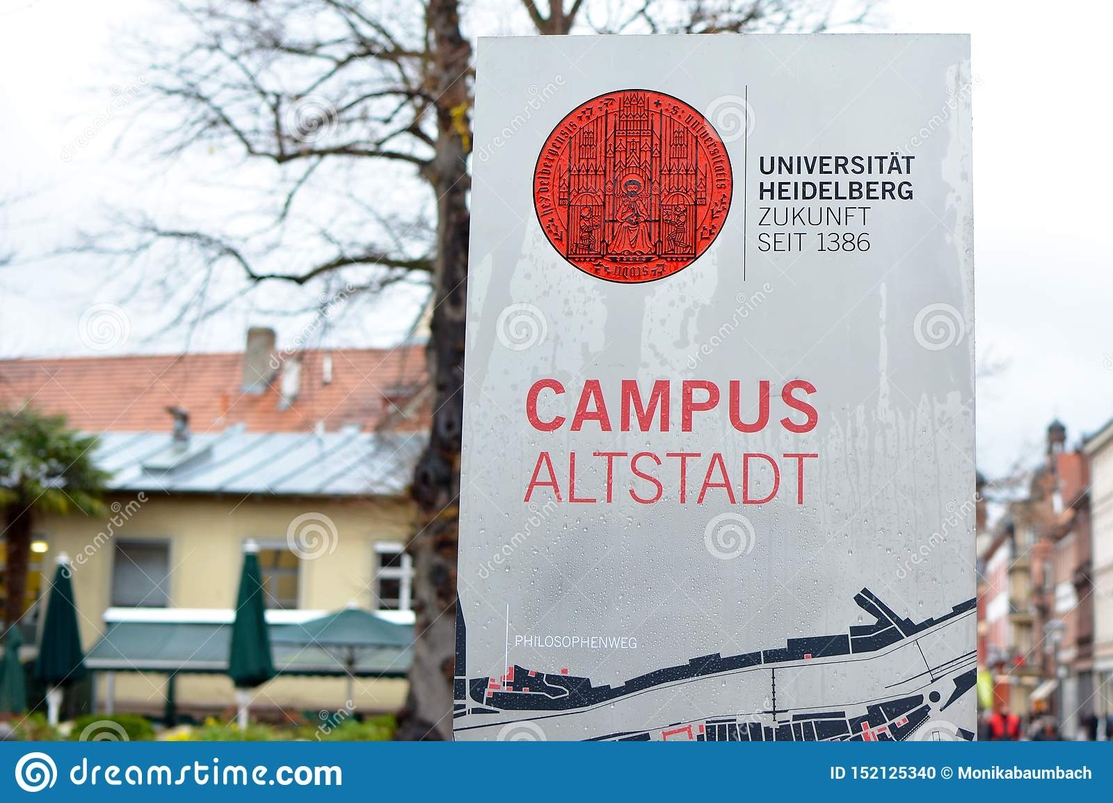 Sign with red university emblem and words `University Heidelberg, future since 1386` and `Campus historic city center` on