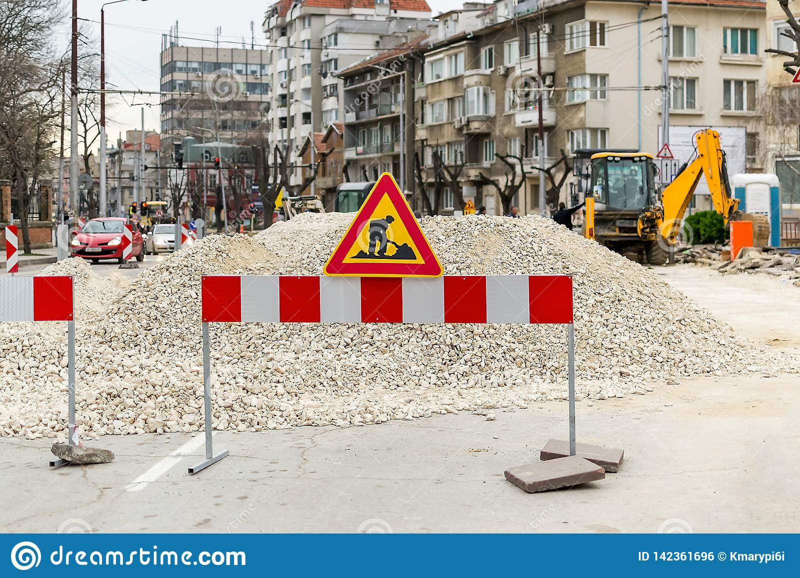 The sign of road works on red white barrier in front of a pile of gravel on a city street. Construction and repair of asphalt