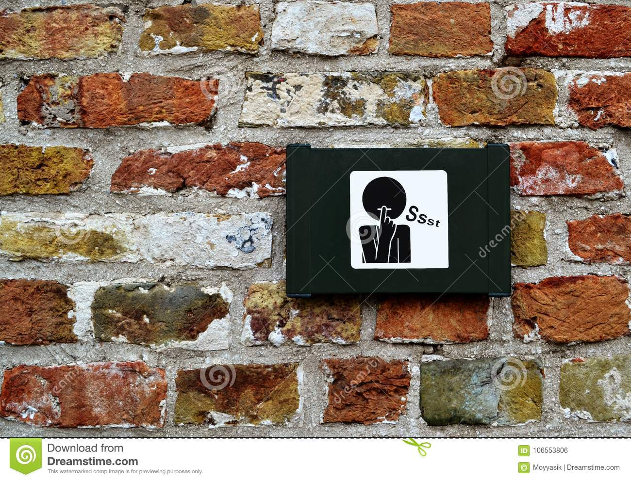Sign/symbol of request for silence/mute on brick wall in Bruges/Brugge, Belgium