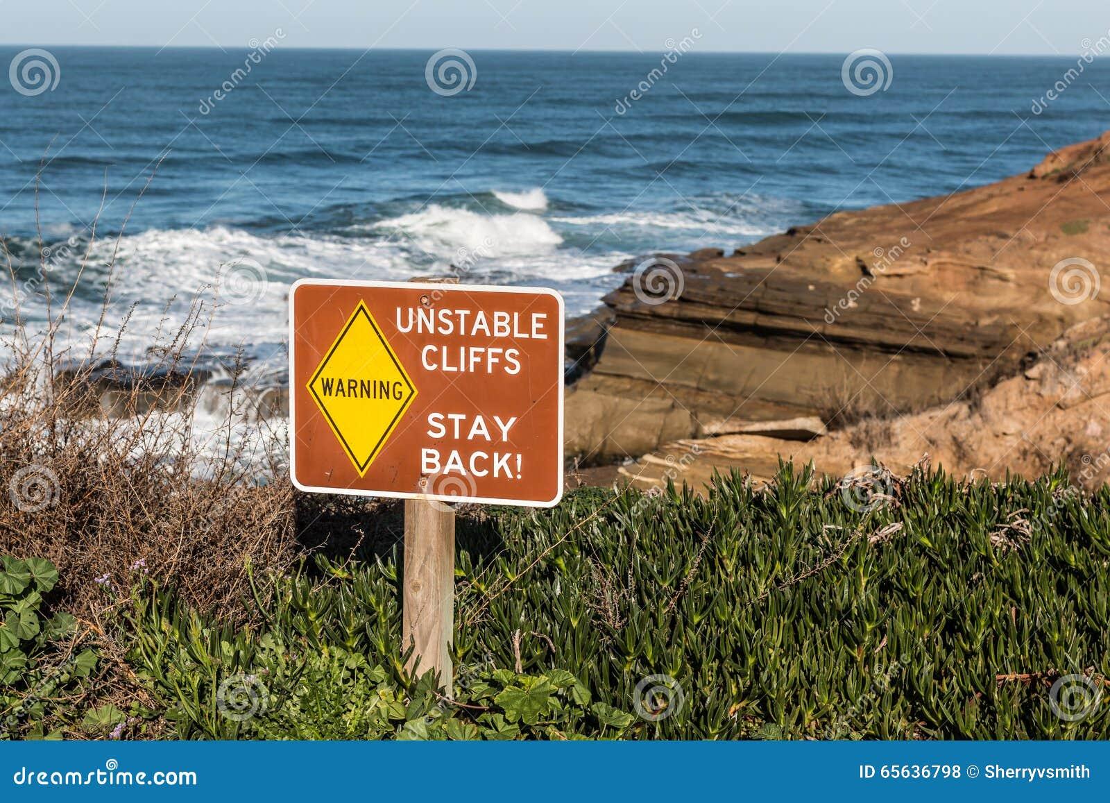 Signe de danger avec des falaises à l arrière-plan aux falaises de coucher du soleil