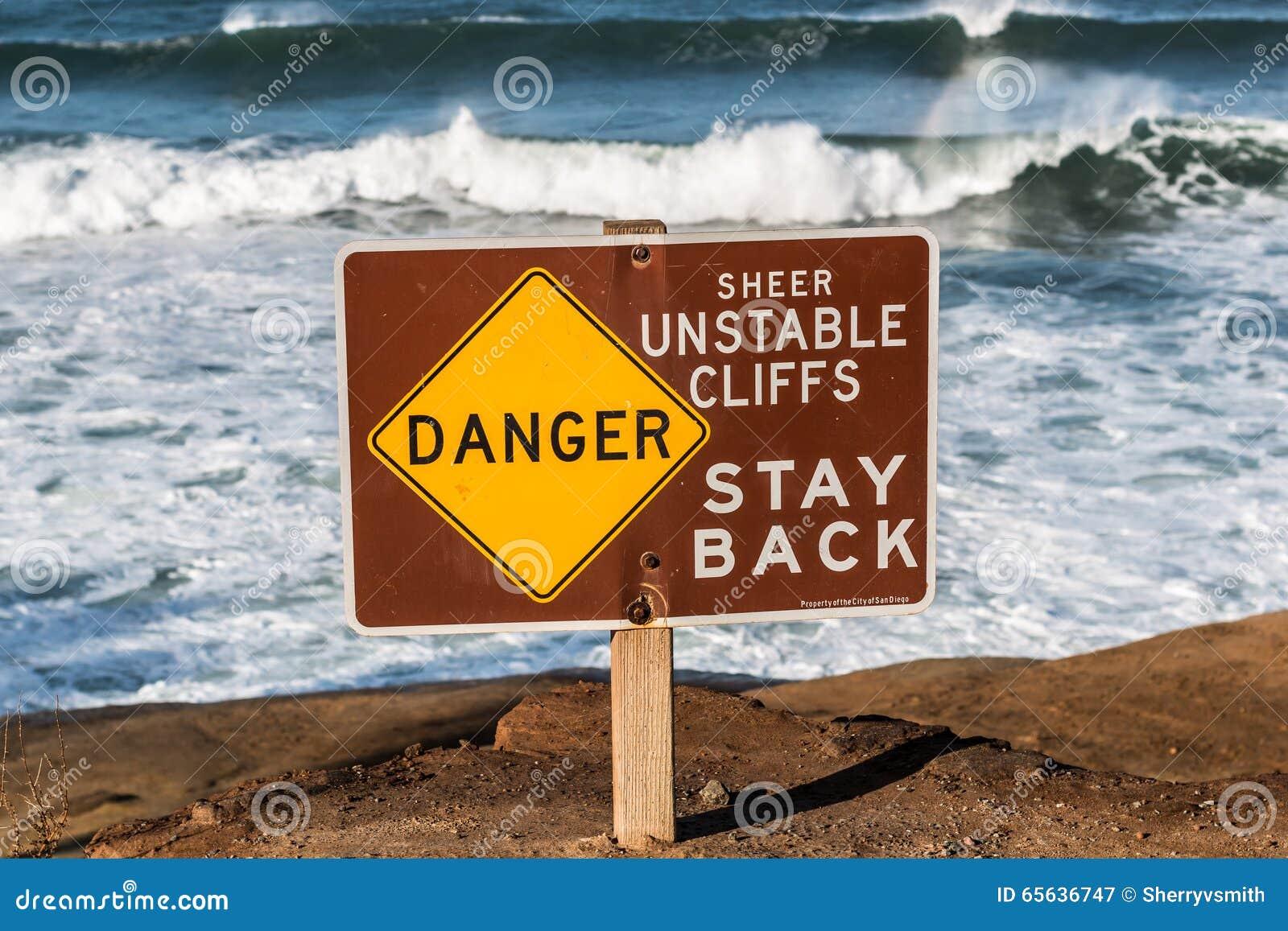 Signe de danger avec des vagues à l arrière-plan aux falaises de coucher du soleil