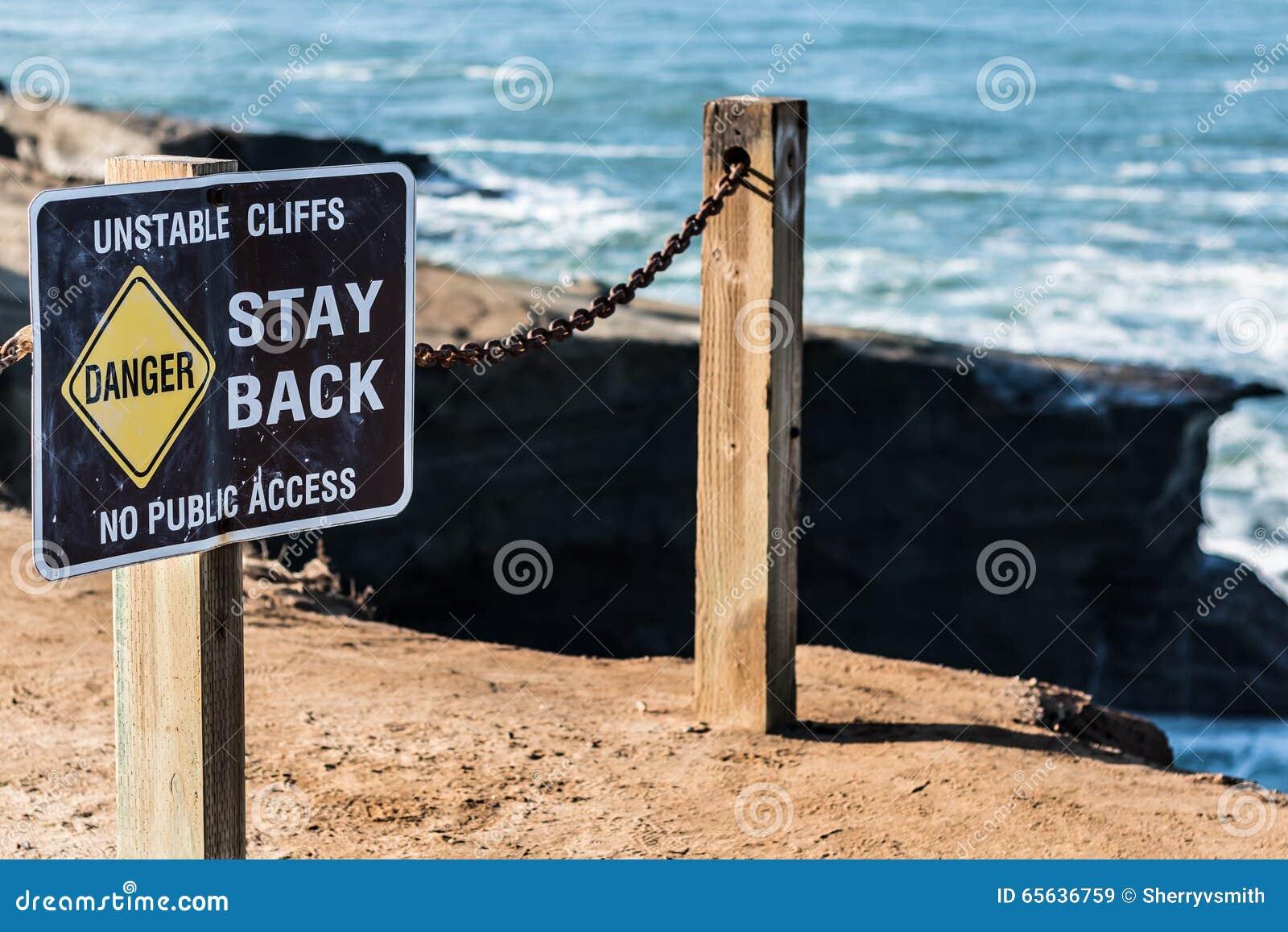 Signe de danger avec la balustrade aux falaises de coucher du soleil