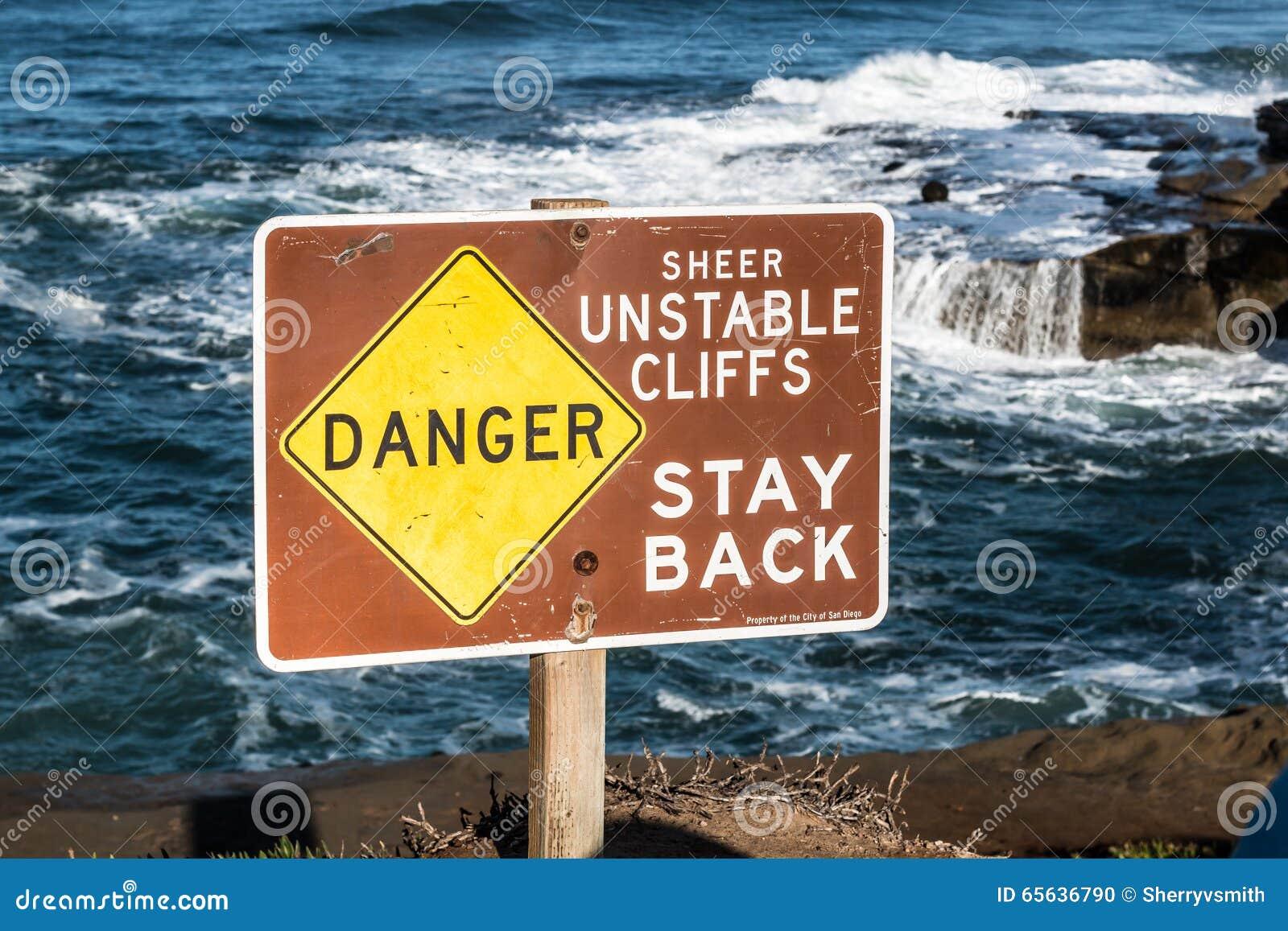 Signe de danger avec le fond d océan aux falaises de coucher du soleil