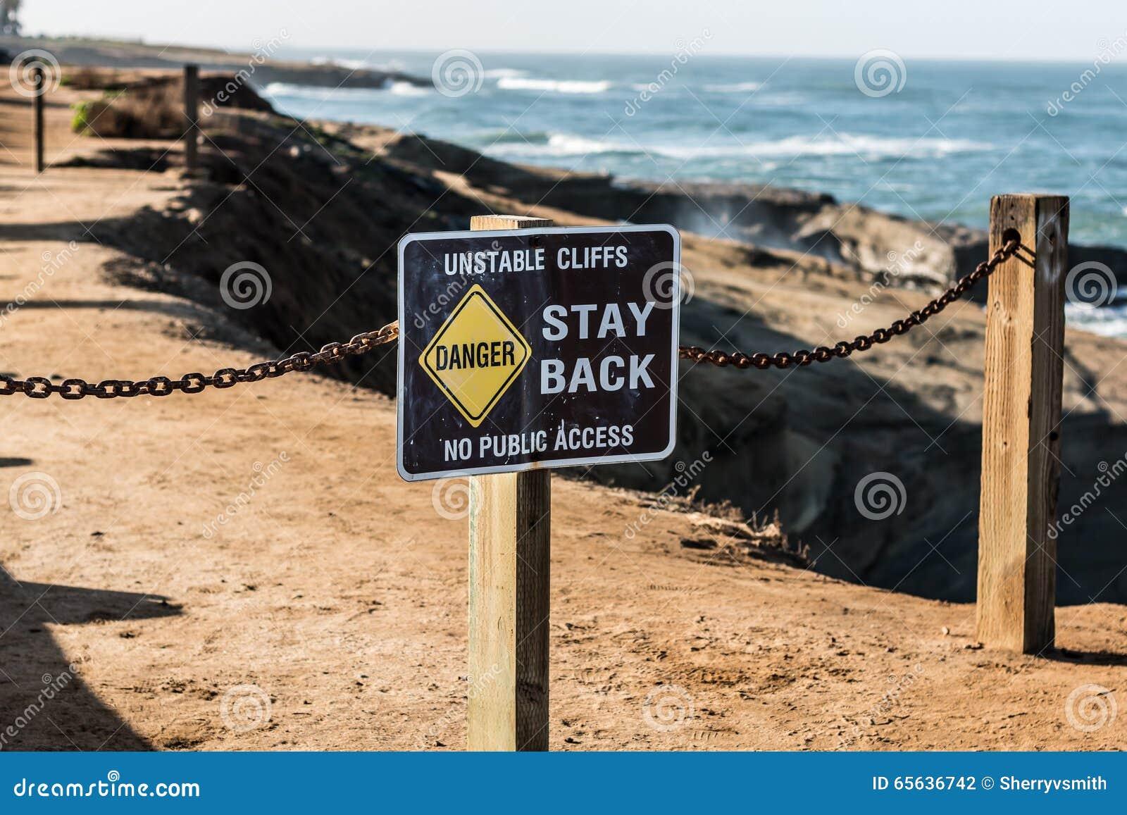 Signe de danger avec le fond de traînée aux falaises de coucher du soleil