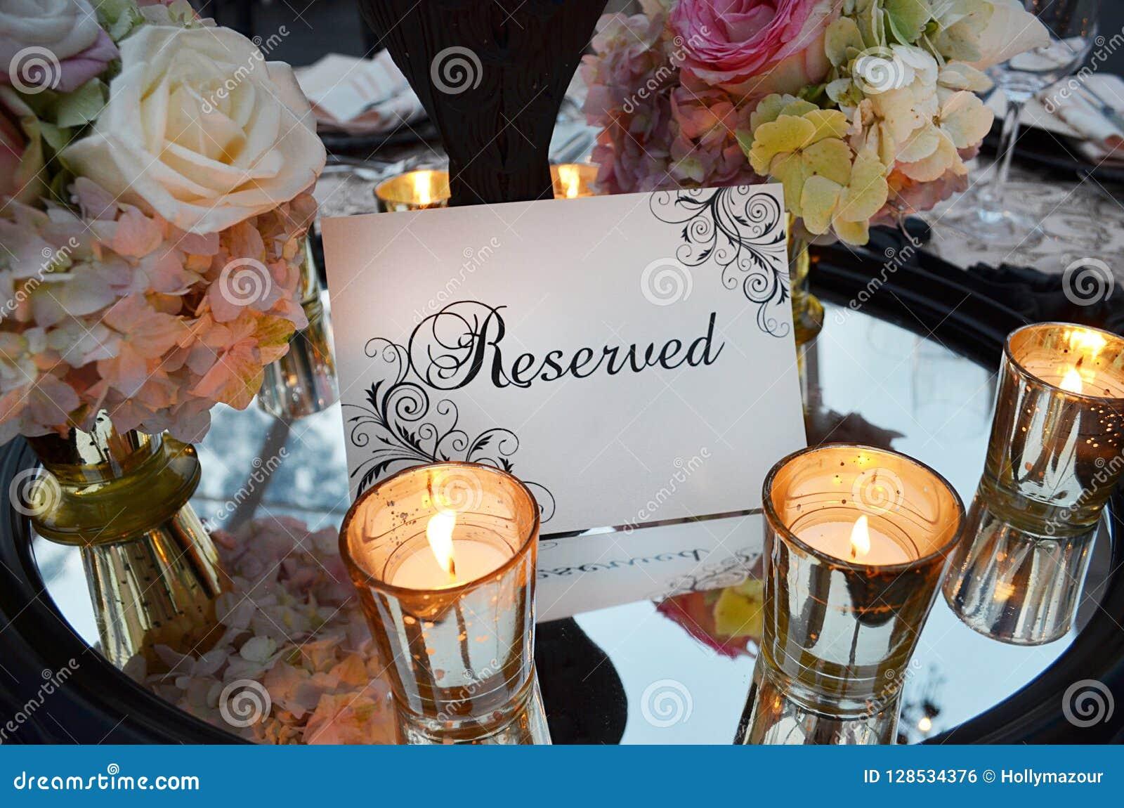 Signe de réservation avec le bouquet de mariage et verres sur la table