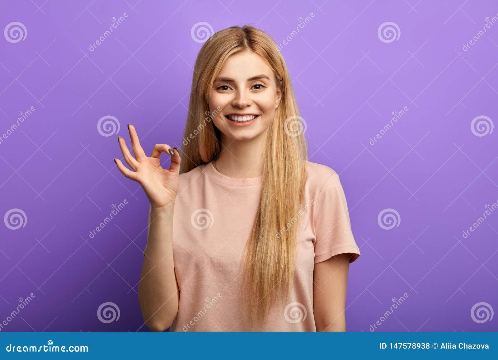 Signe enthousiaste de sourire heureux attrayant d ok d apparence de femme