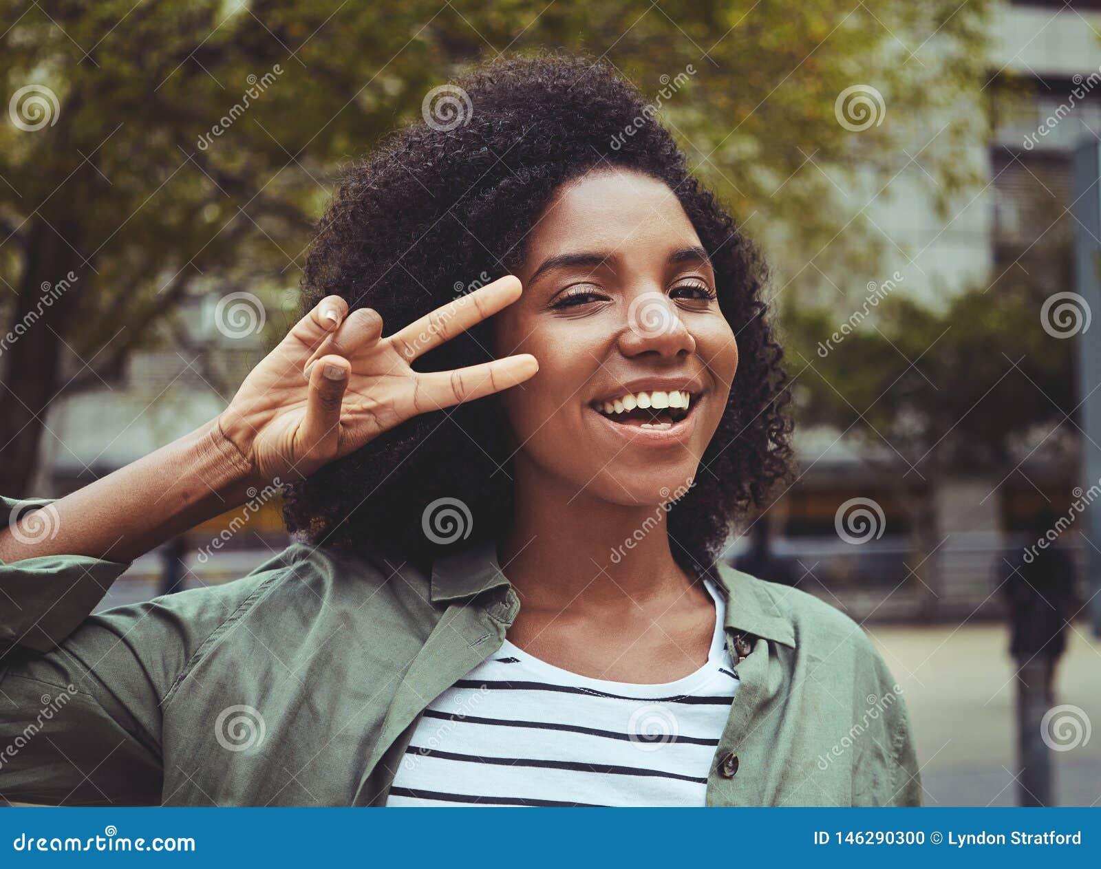 Signo de la paz sonriente de la demostración de la mujer joven
