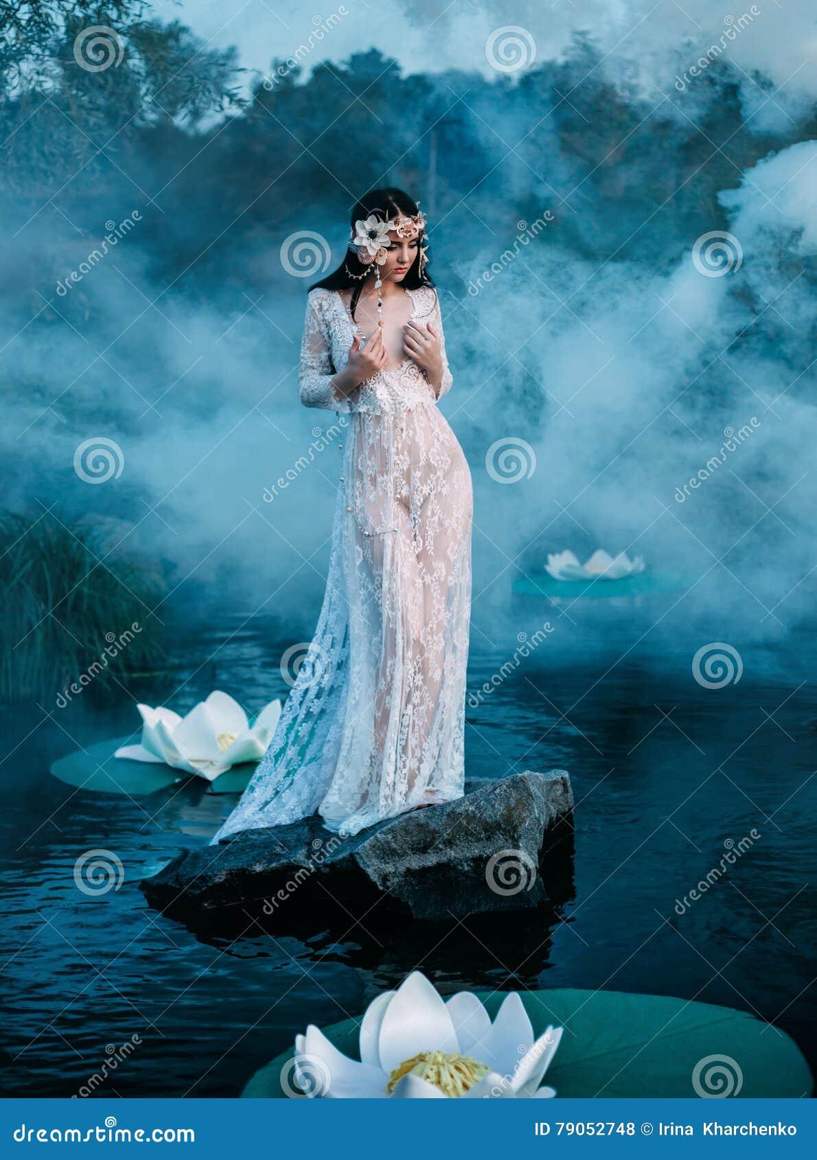 Signora affascinante, stante su una roccia enorme nel mezzo del lago