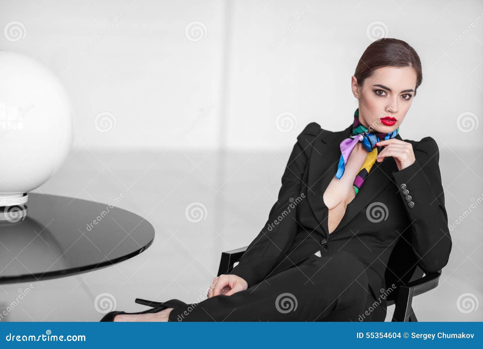Signora alla moda di affari in vestito nero nell interno minimalistic