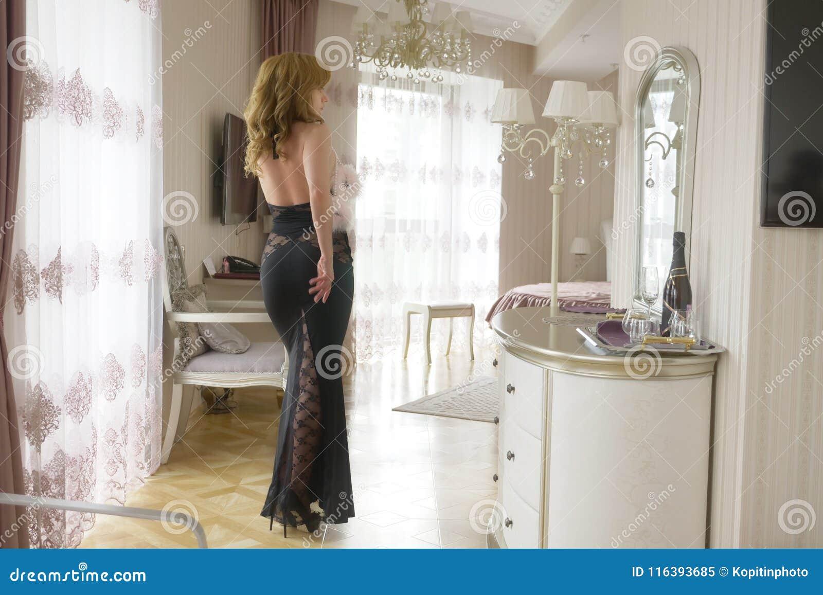 e7f26fdc1849 Signora alla moda si è vestita nell uguagliare il vestito nero dal pizzo  Giovane donna che posa nella posa sensuale che tiene le manette lanuginose  rosa in ...