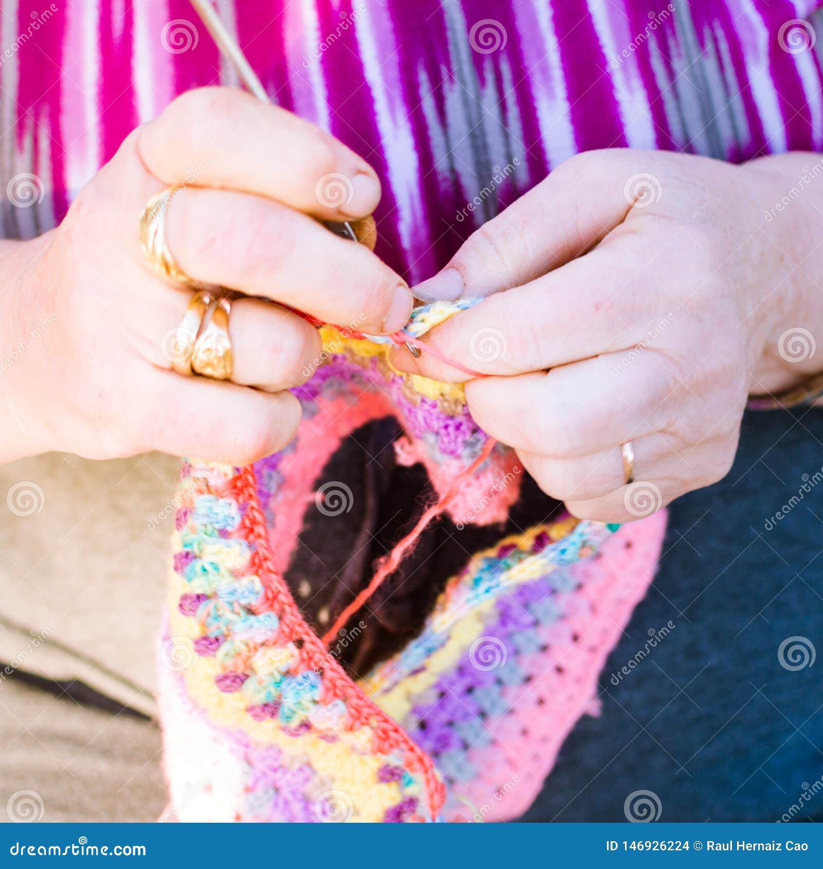 Signora anziana che tricotta sui ferri da maglia, facendo uso della lana variopinta Hobby per la gente anziana