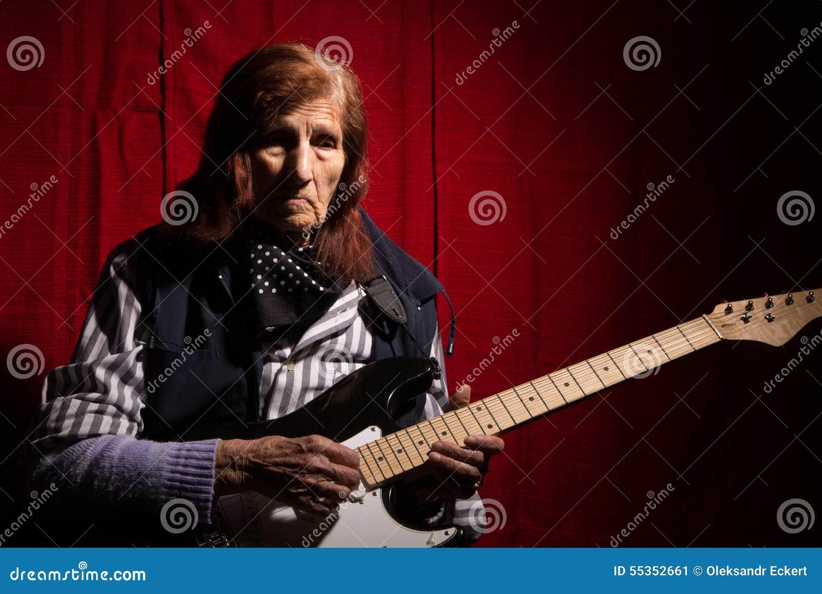 Signora anziana divertente che gioca chitarra elettrica