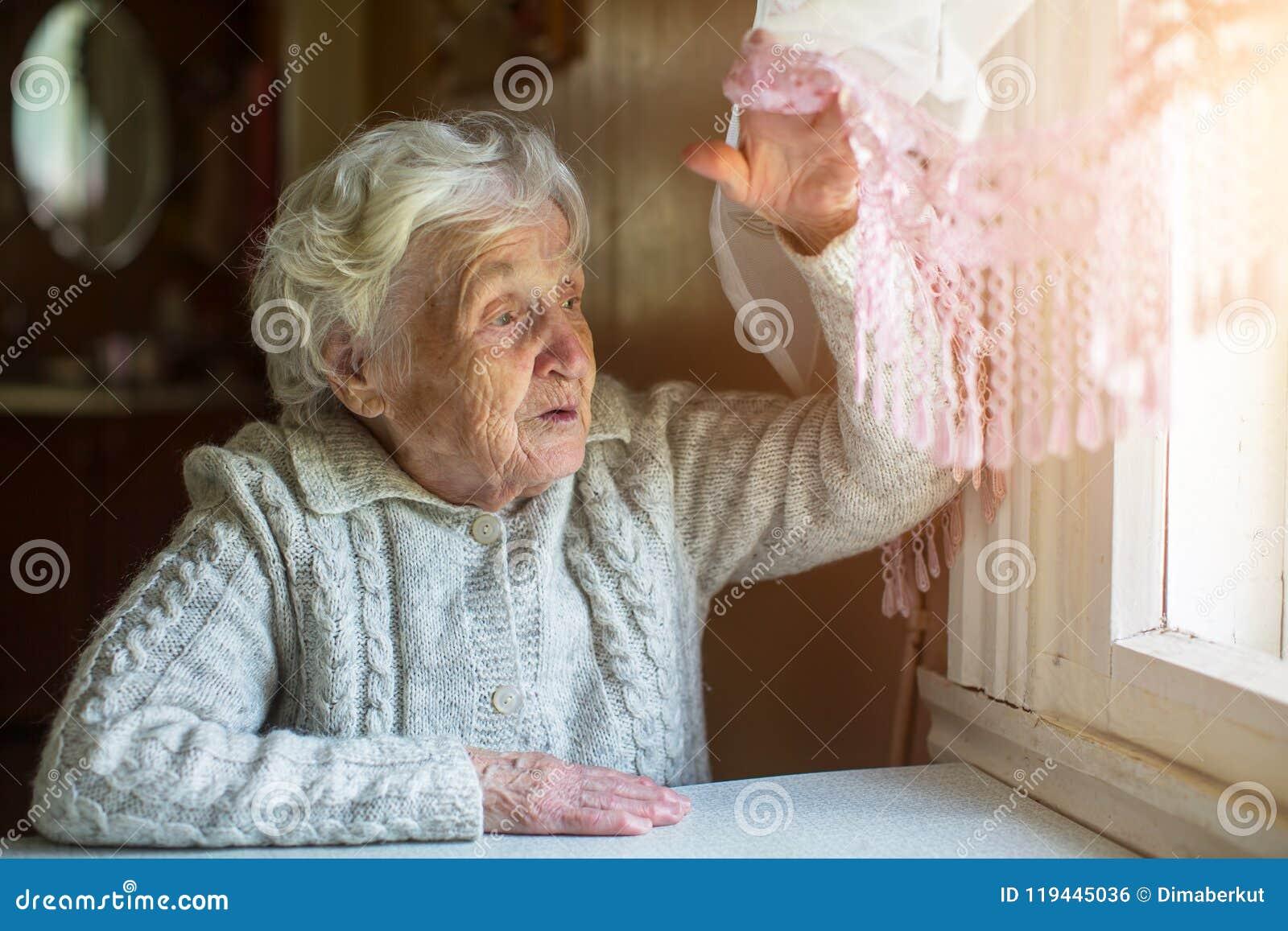 Signora anziana guarda dalla finestra