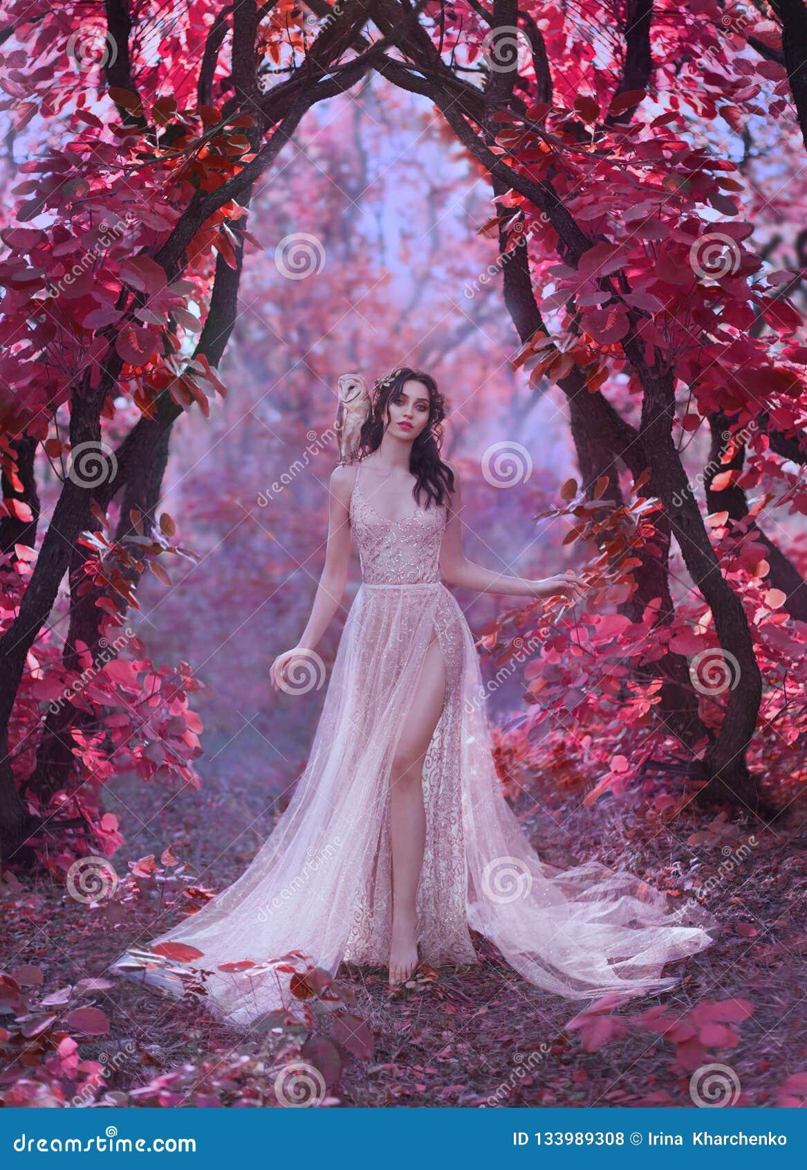 Signora attraente misteriosa in un vestito di lusso leggero lungo in una foresta rosa magica, portone al mondo di fiaba, sveglio