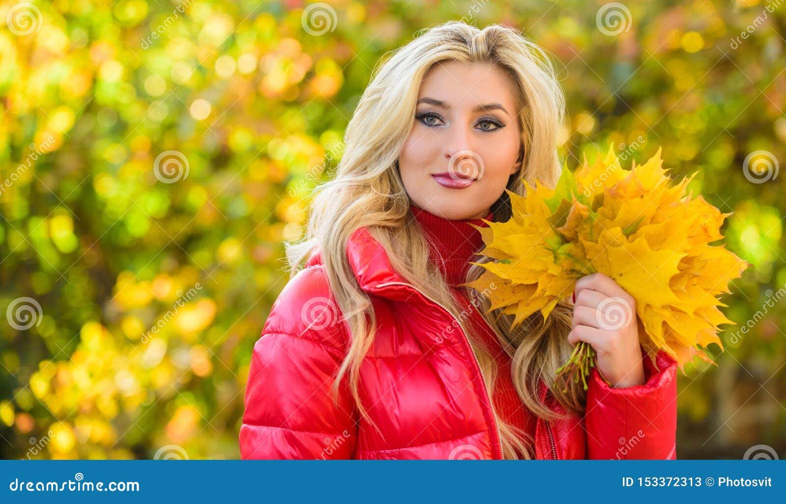Signora che posa con il fondo autunnale della natura delle foglie Foglie gialle dell acero cadute mazzo vago biondo della tenuta