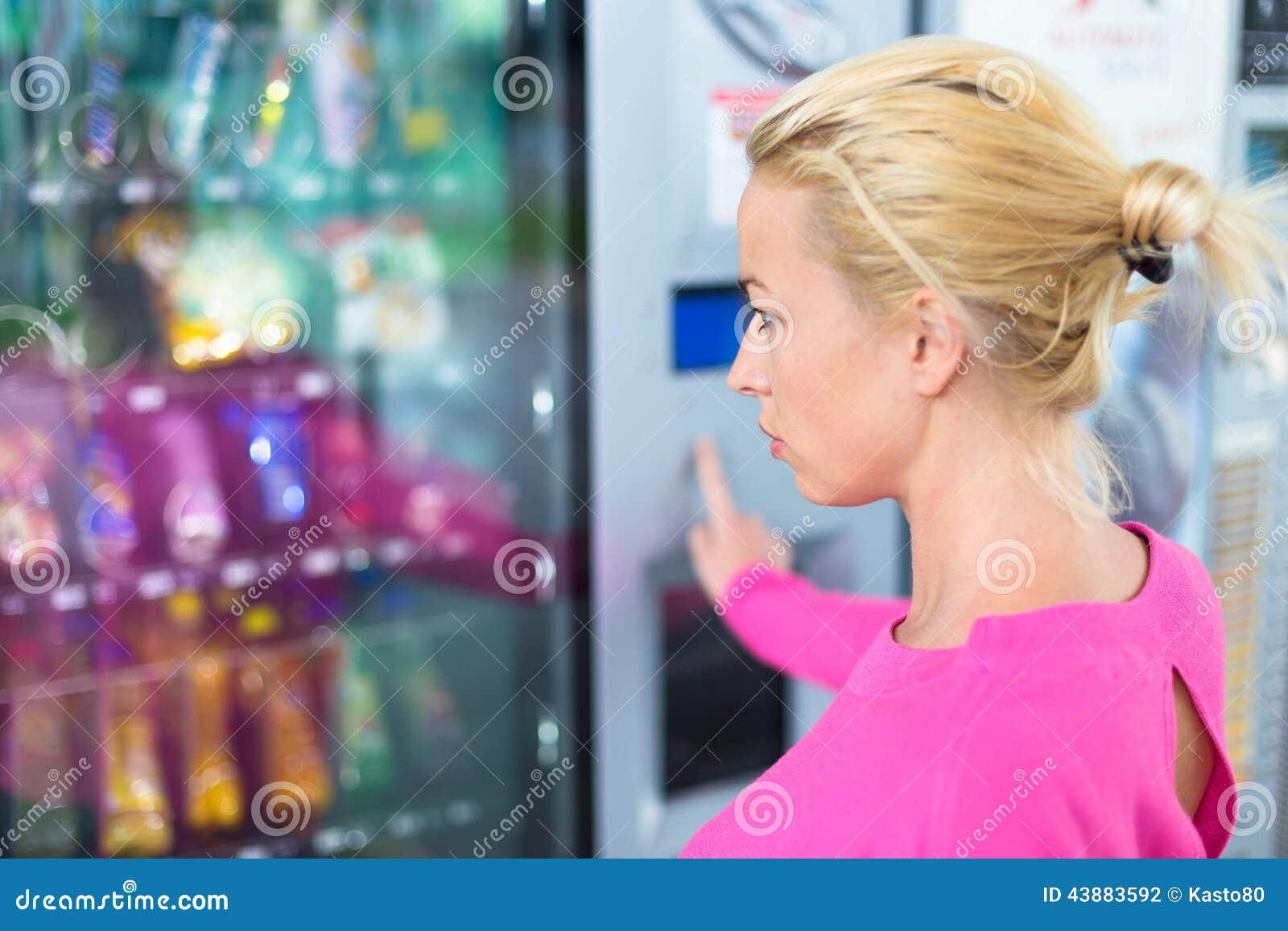 Signora che usando un distributore automatico moderno