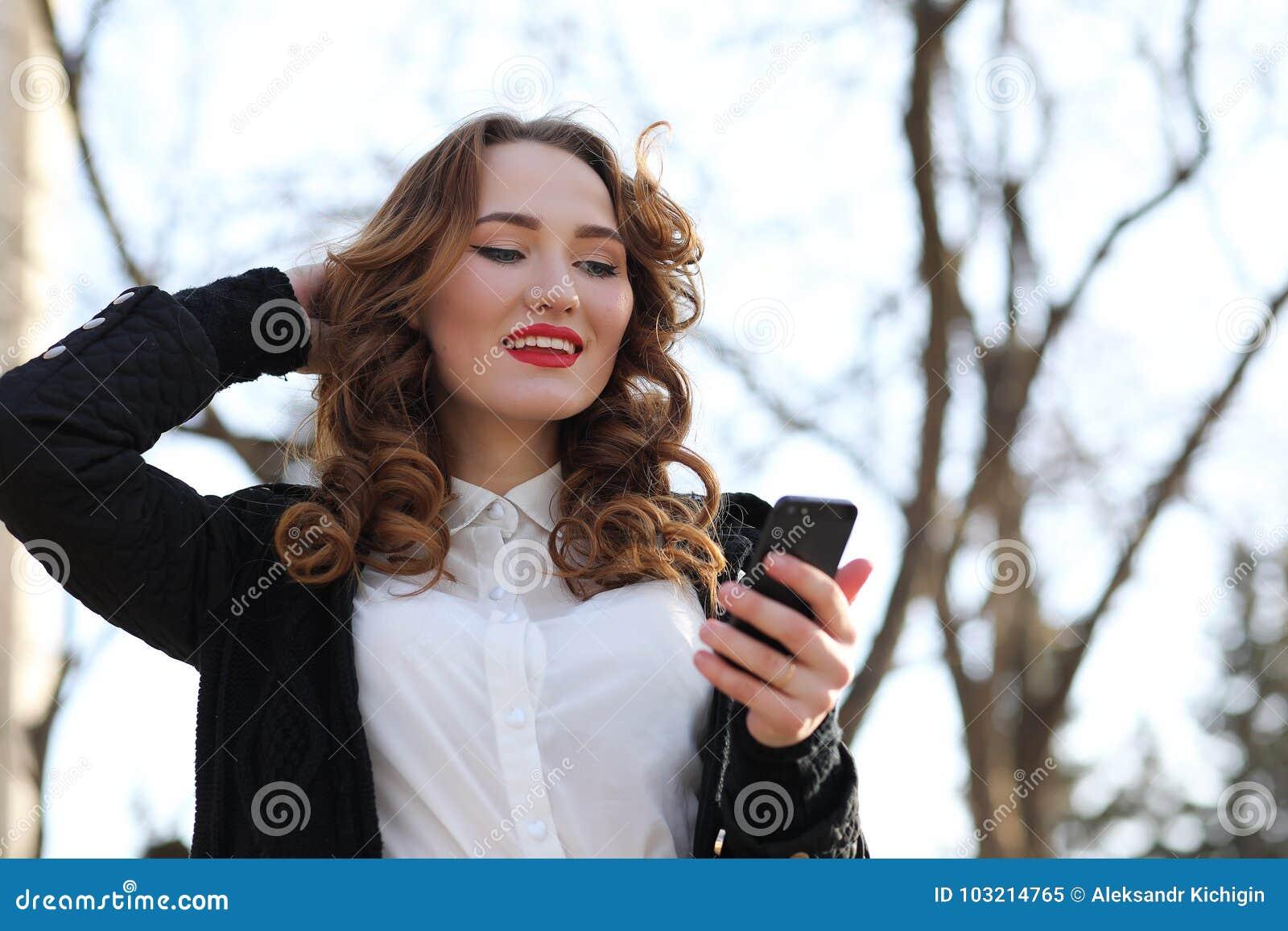 Signora di affari in un vestito all aperto con il telefono cellulare