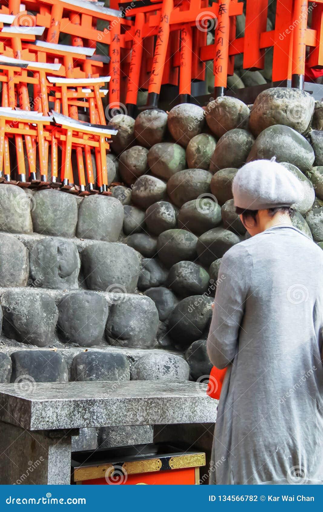 Signora giapponese che prega al santuario di Fushimi Inari Taisha