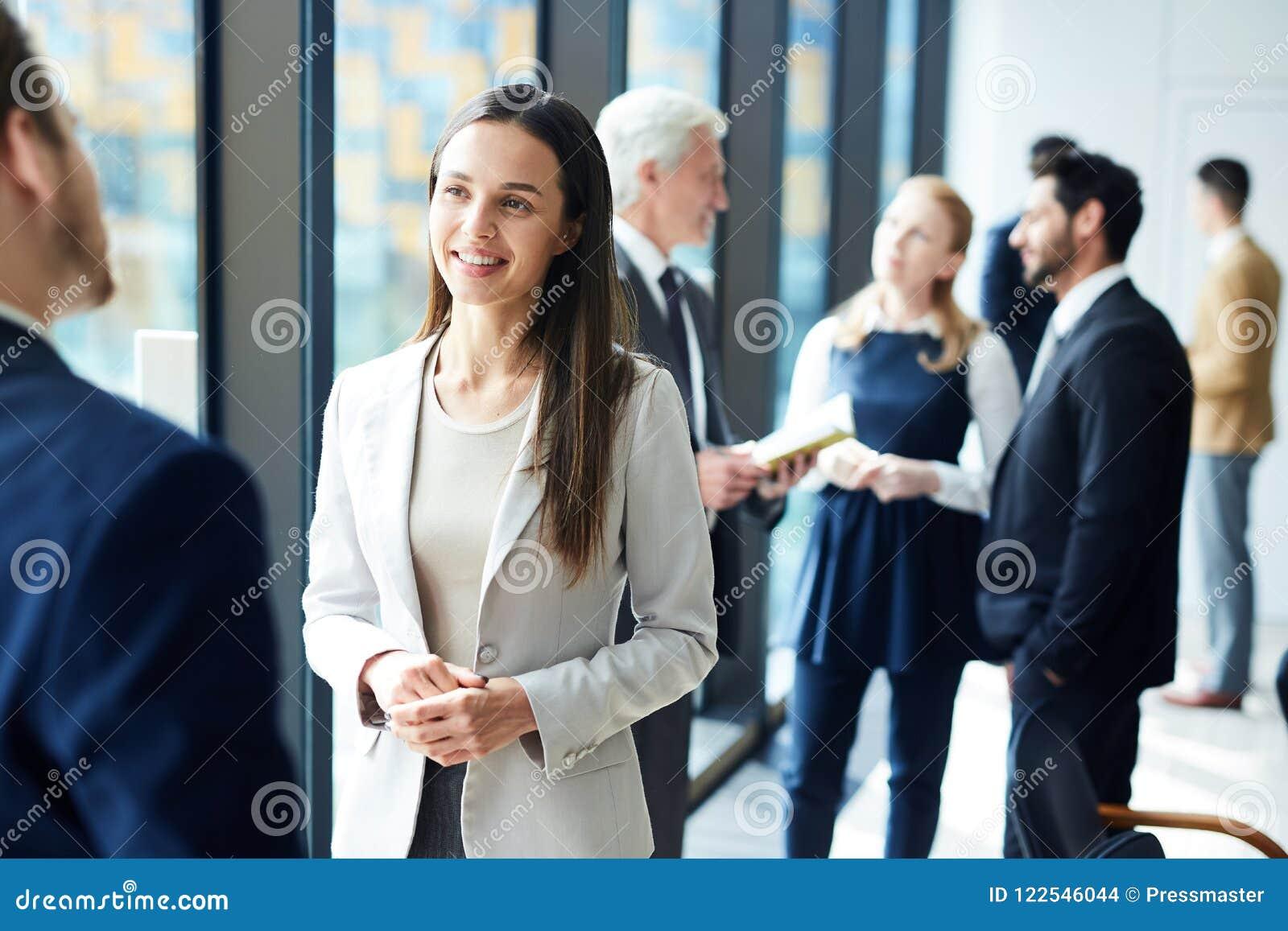 Signora graziosa di affari che parla con collega