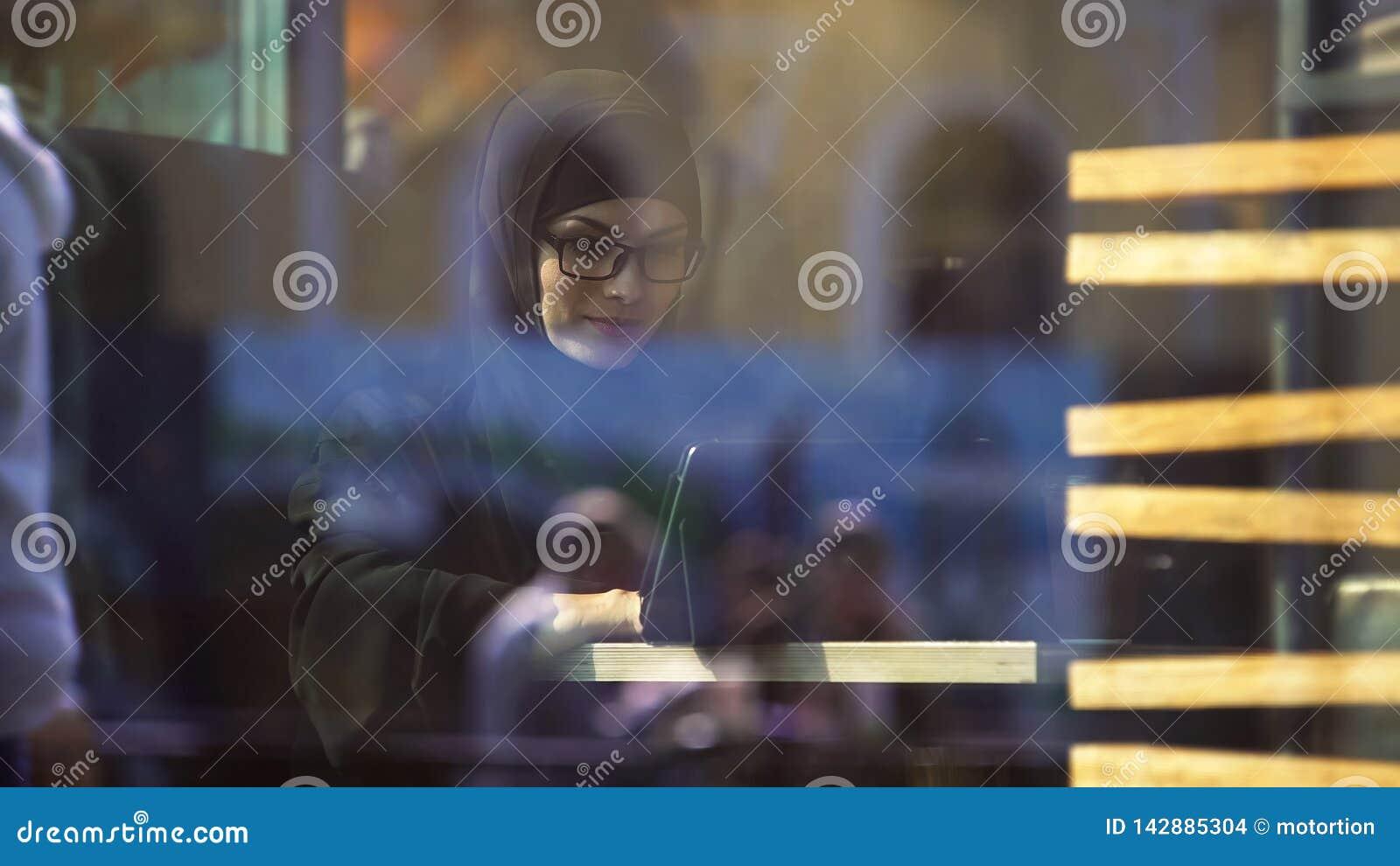Signora musulmana in abbigliamento tradizionale che chiacchiera sulla linguetta che si siede in caffè, vita moderna